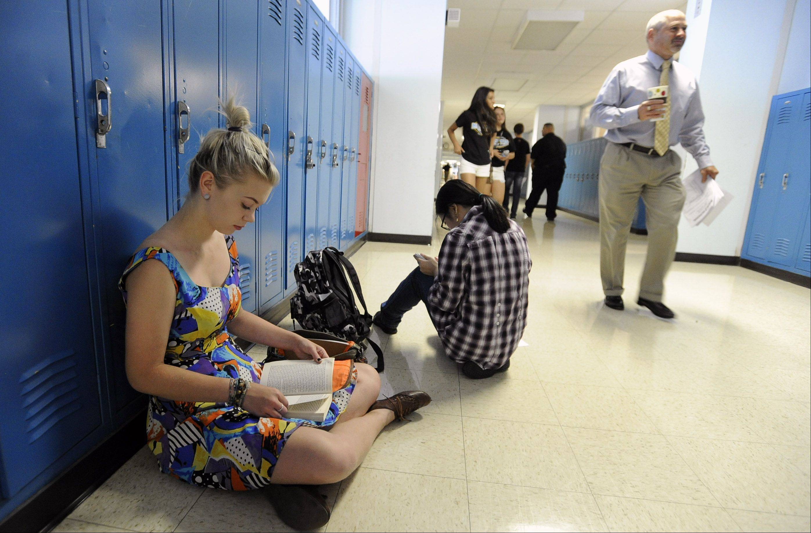 Maine West High School junior Danni Schanmier, 16, takes time to read a book before heading off to class on her first day back Monday.