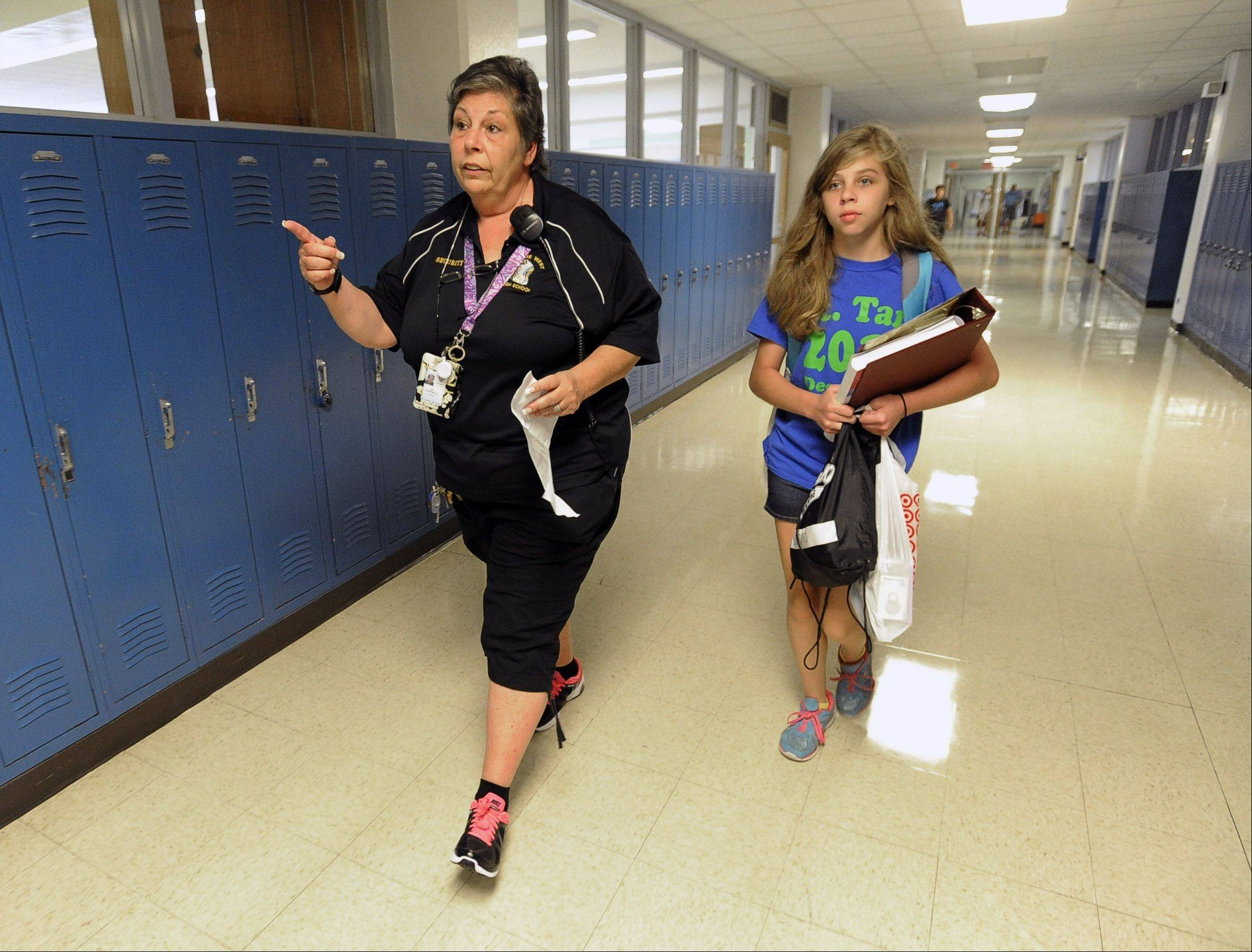 Security officer Karen Lindermuth helps freshman Kathleen Saverino, 14, to her locker Monday on her first of classes at Maine West High School in Des Plaines.