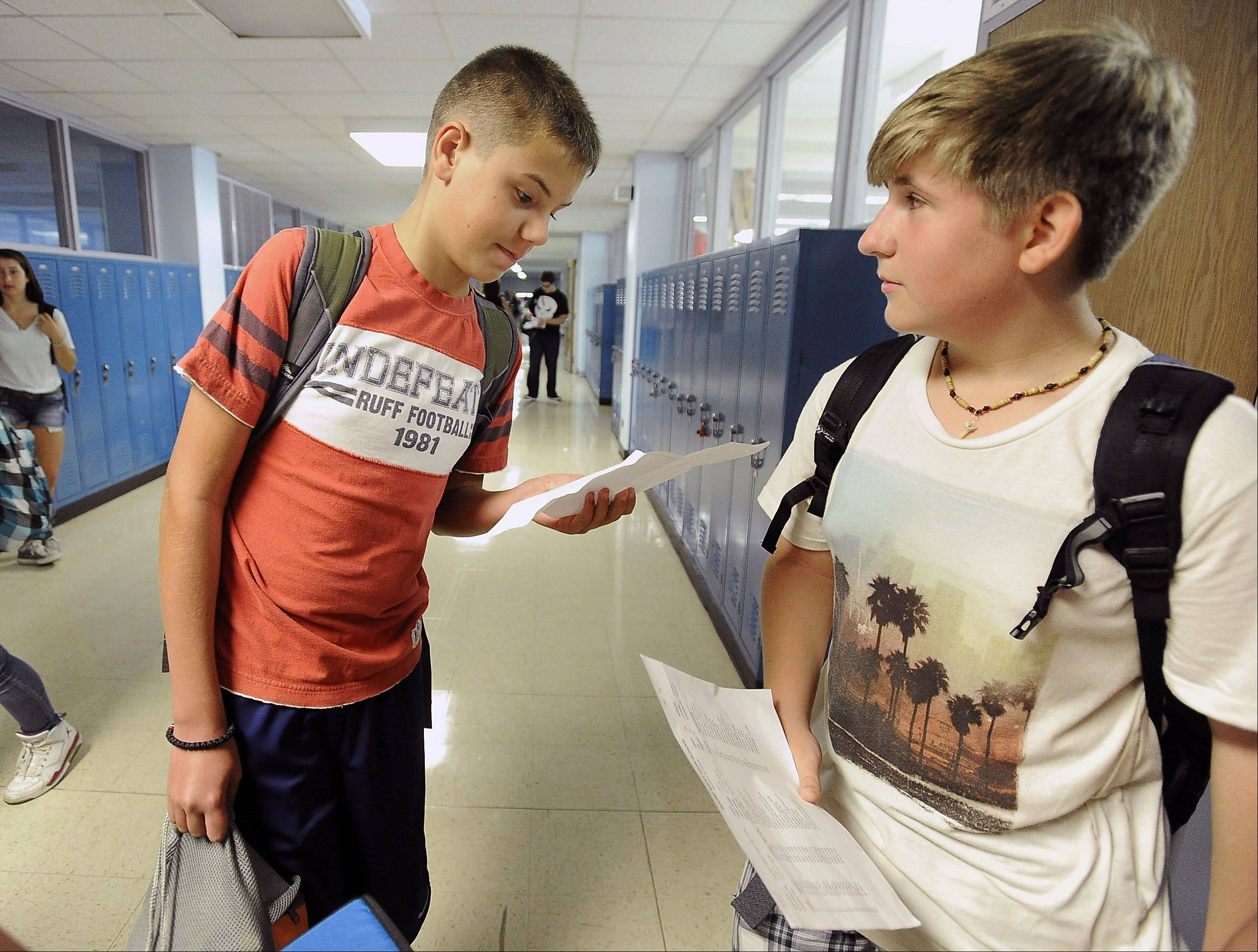 Djordje Lojanica, 14, and his friend Lucas Rychtarczyk, 14, compare schedules in the Maine West High School hallway on their first day back to school on Monday.