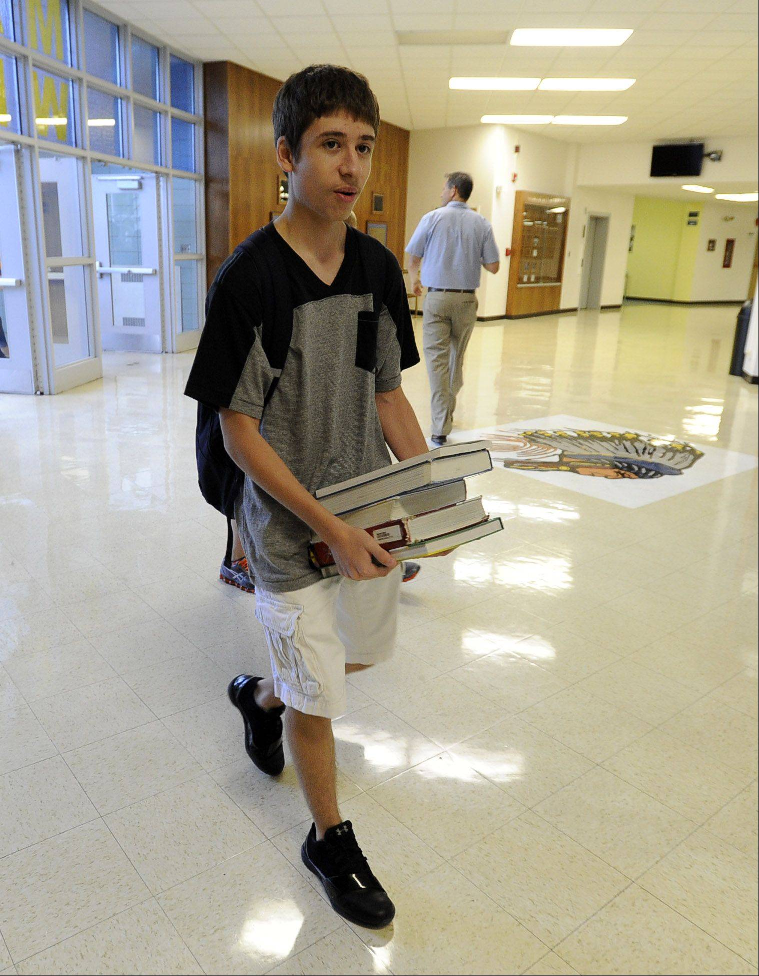 Denis Vujic, 16, a junior, carries his books to class Monday on his first day back at Maine West High School in Des Plaines.