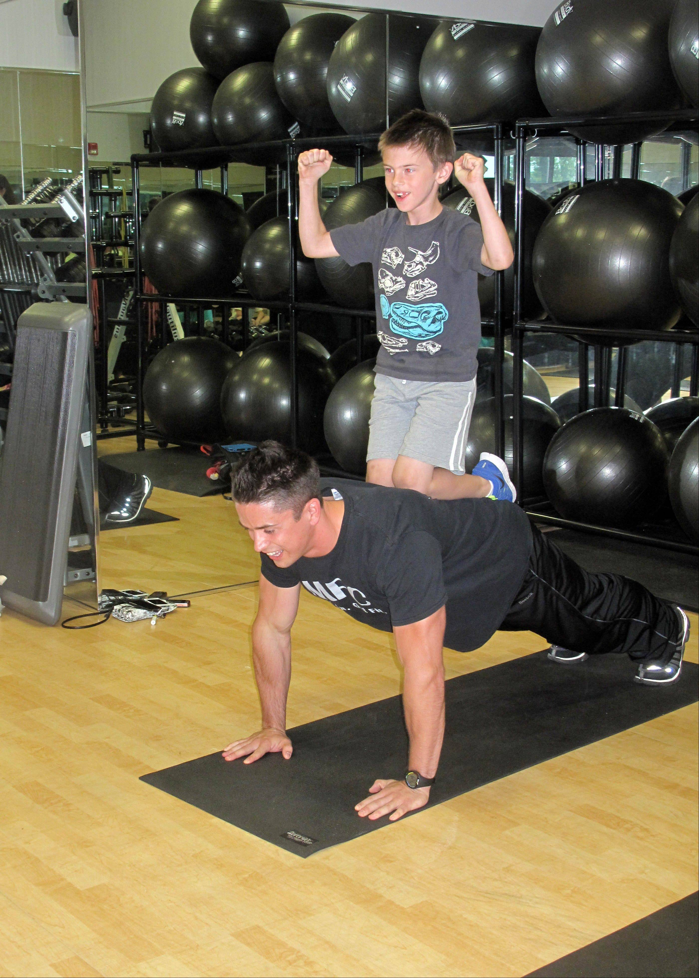 Joe McCarthy, 7, makes a muscle atop Shane Herman, co-owner of Midwest Fit Club in Naperville, during the gym's first Big Push-ups for Little Friends fundraiser, a 24-hour event involving 327 people that raised more than $1,500.