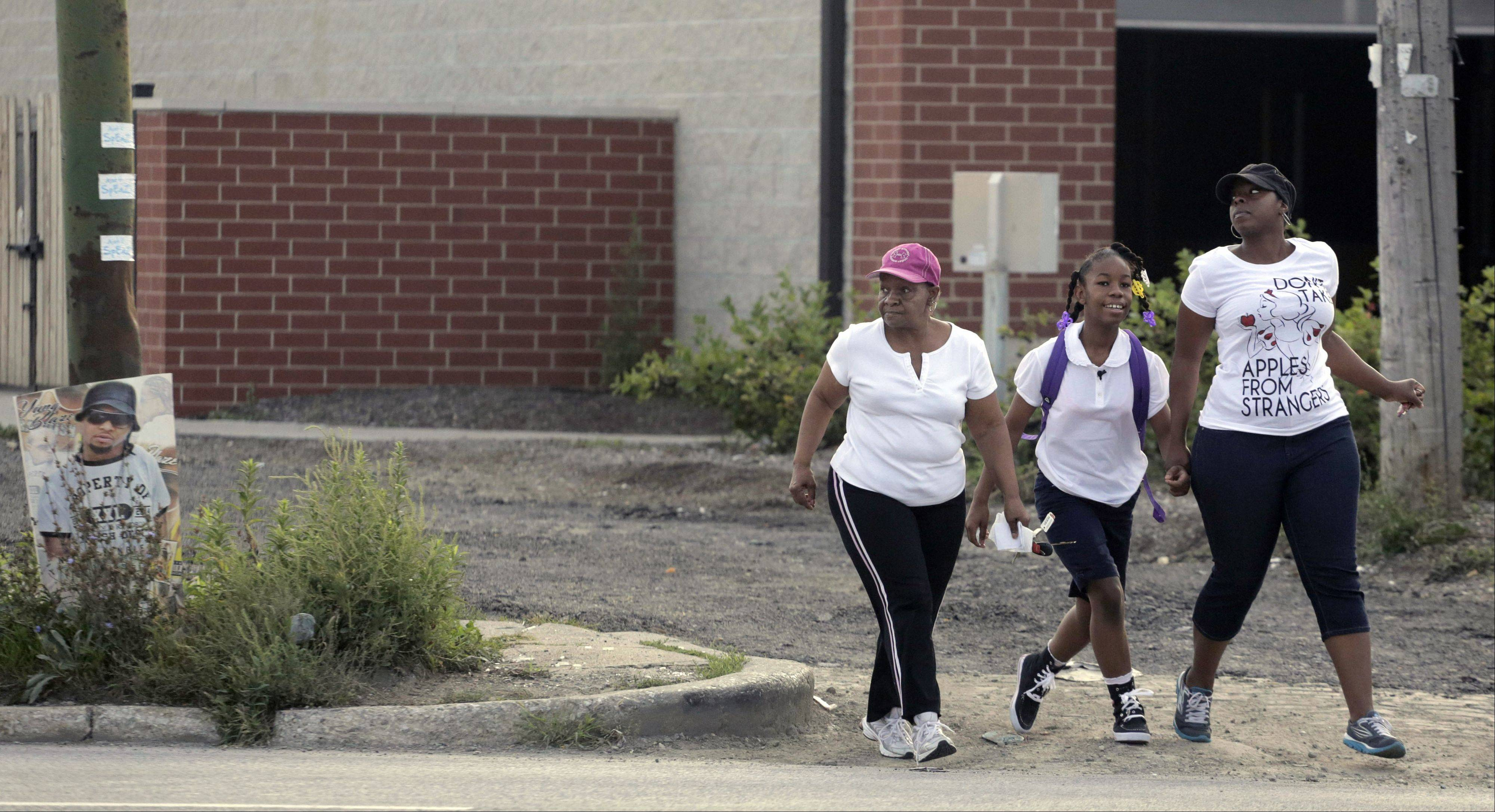 Annie Stovall, left, walks with her daughter Crystal Stovall, right, and her granddaughter Kayla Porter to Gresham Elementary School on the first day of classes Monday. The school that Kayla attended last year was closed over the summer by Chicago Public Schools.