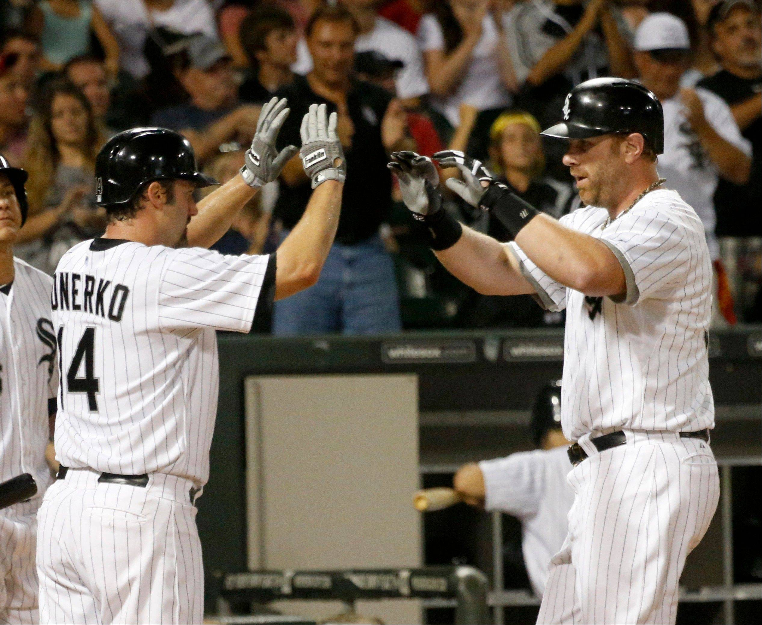 Paul Konerko (14) greets Adam Dunn at home after the pair scored on Dunn's two-run homer off Houston Astros relief pitcher Brett Oberholtzer during the sixth inning Monday in Chicago.