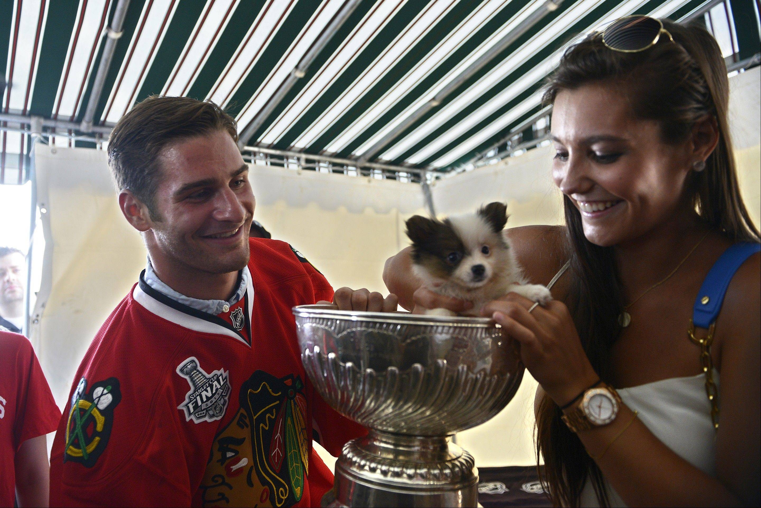 "Pittsburgh native Brandon Saad of the Chicago Blackhawks and his girlfriend, Alyssa Wozniak, 20, put ""Bella"" a puppy in the Stanley Cup during a celebration in Gibsonia where Saad brought the cup to share with friends, family and neighbors on Thursday."