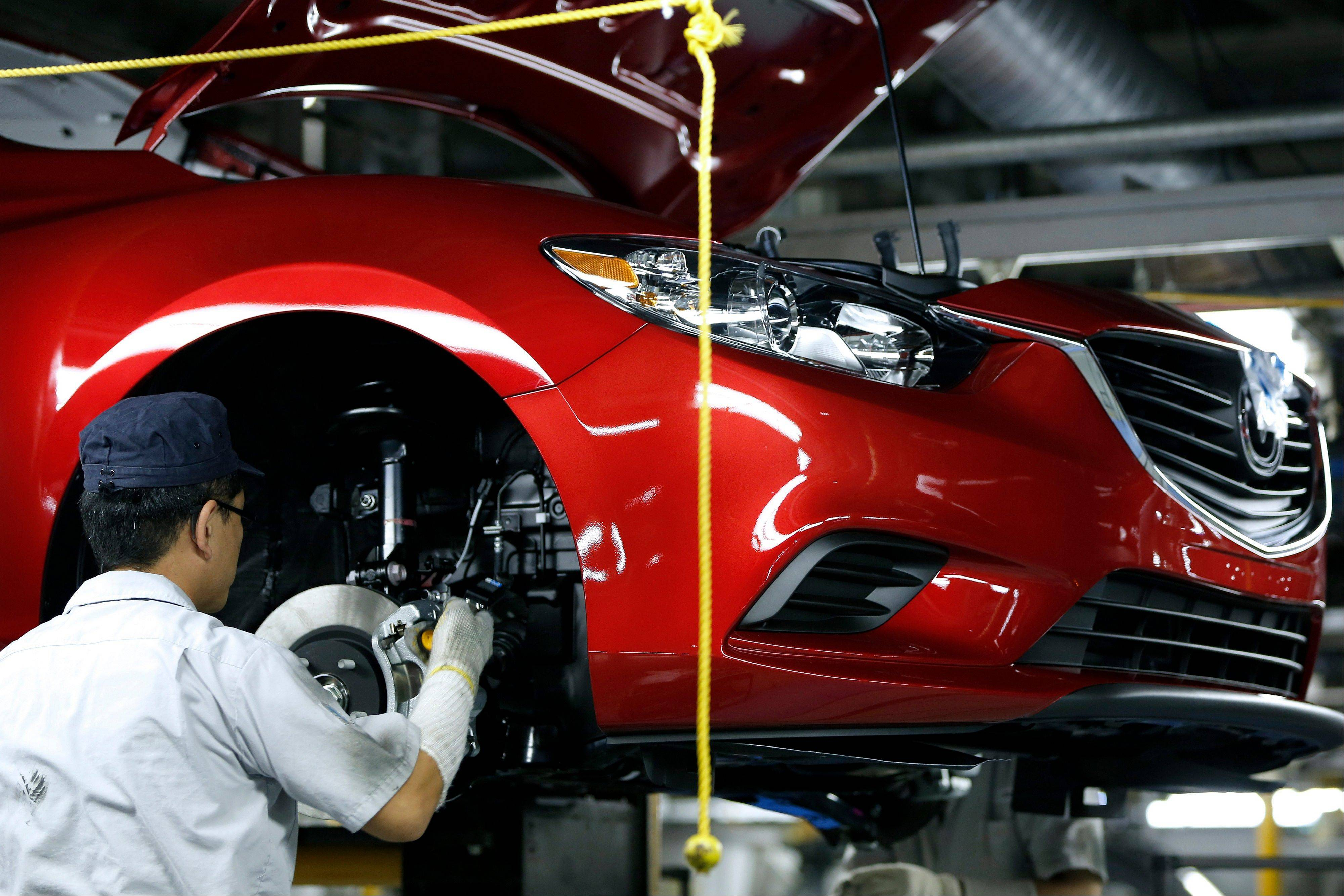 An employee assembles a Mazda Motor Corp. Atenza sedan (Mazda 6) on the production line at the company�s plant in Hofu, Yamaguchi Prefecture, Japan, on Tuesday, Aug. 27, 2013. Mazda is Japan�s most export-dependent carmaker.