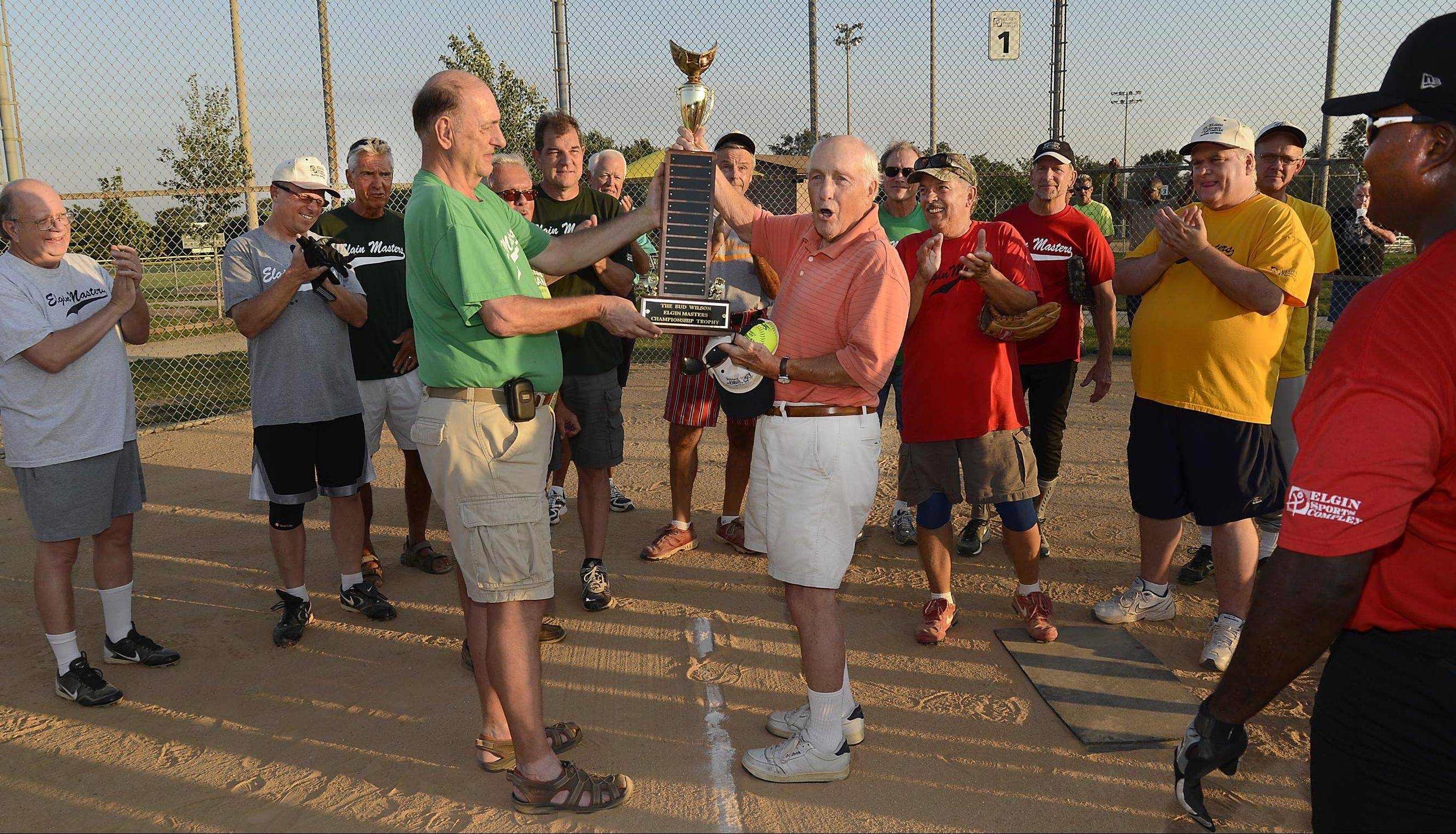 "Bud Wilson yells ""Play Ball"" as he is honored with a trophy to thank him for starting and keeping the Elgin Masters Softball League running since 1984. The six-team league plays Tuesday and Thursday nights at the Elgin Sports Complex, and members of each team were present for the event. The league started its playoff tournament after Wilson threw out the first pitch Tuesday."