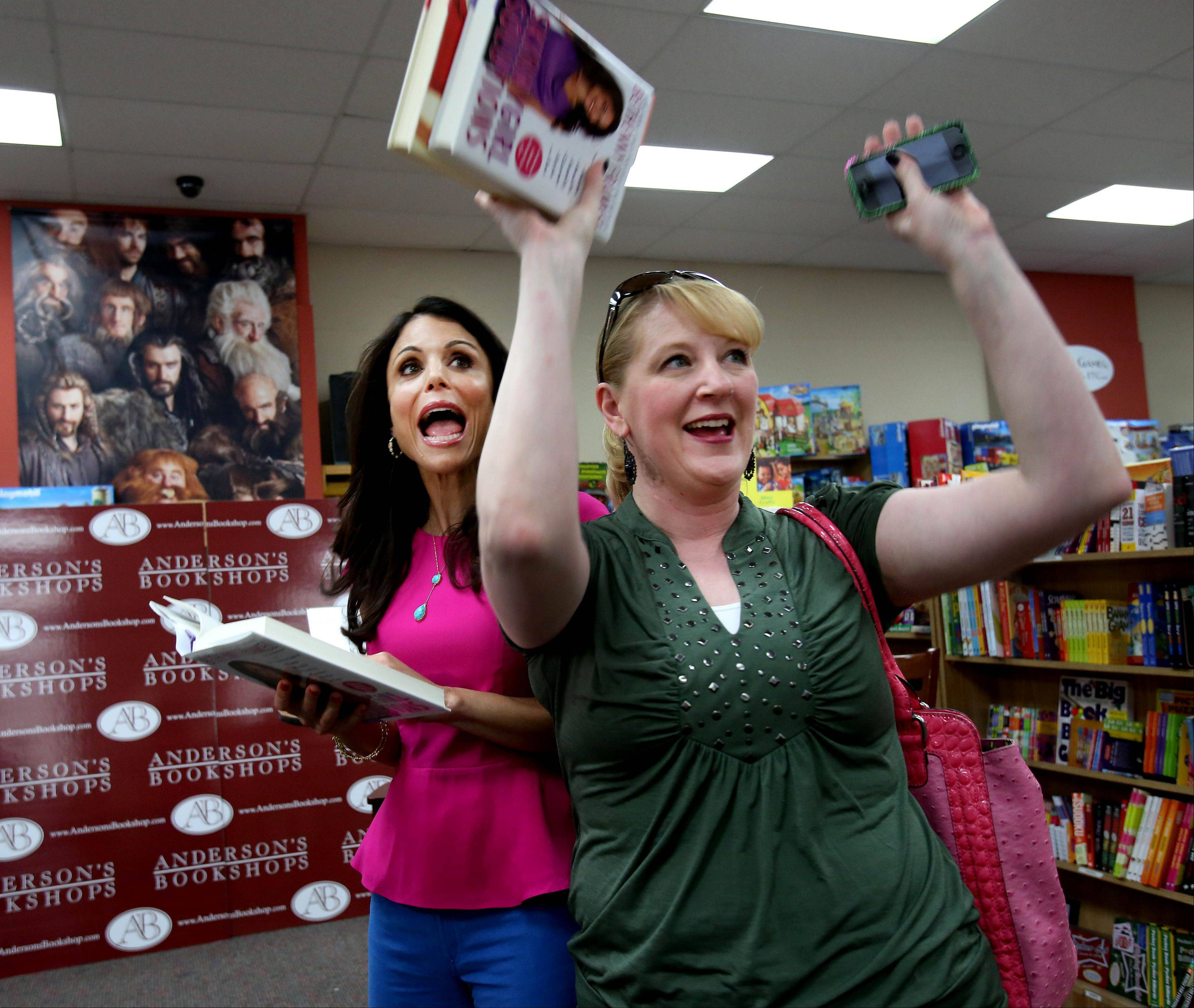 "Jennifer Evers of Naperville celebrates with talk show host and Skinnygirl brand creator Bethenny Frankel after Evers won a trip to New York City to attend the filming of Frankel's talk show ""bethenny"" during an event Tuesday at Anderson's Bookshop in downtown Naperville."