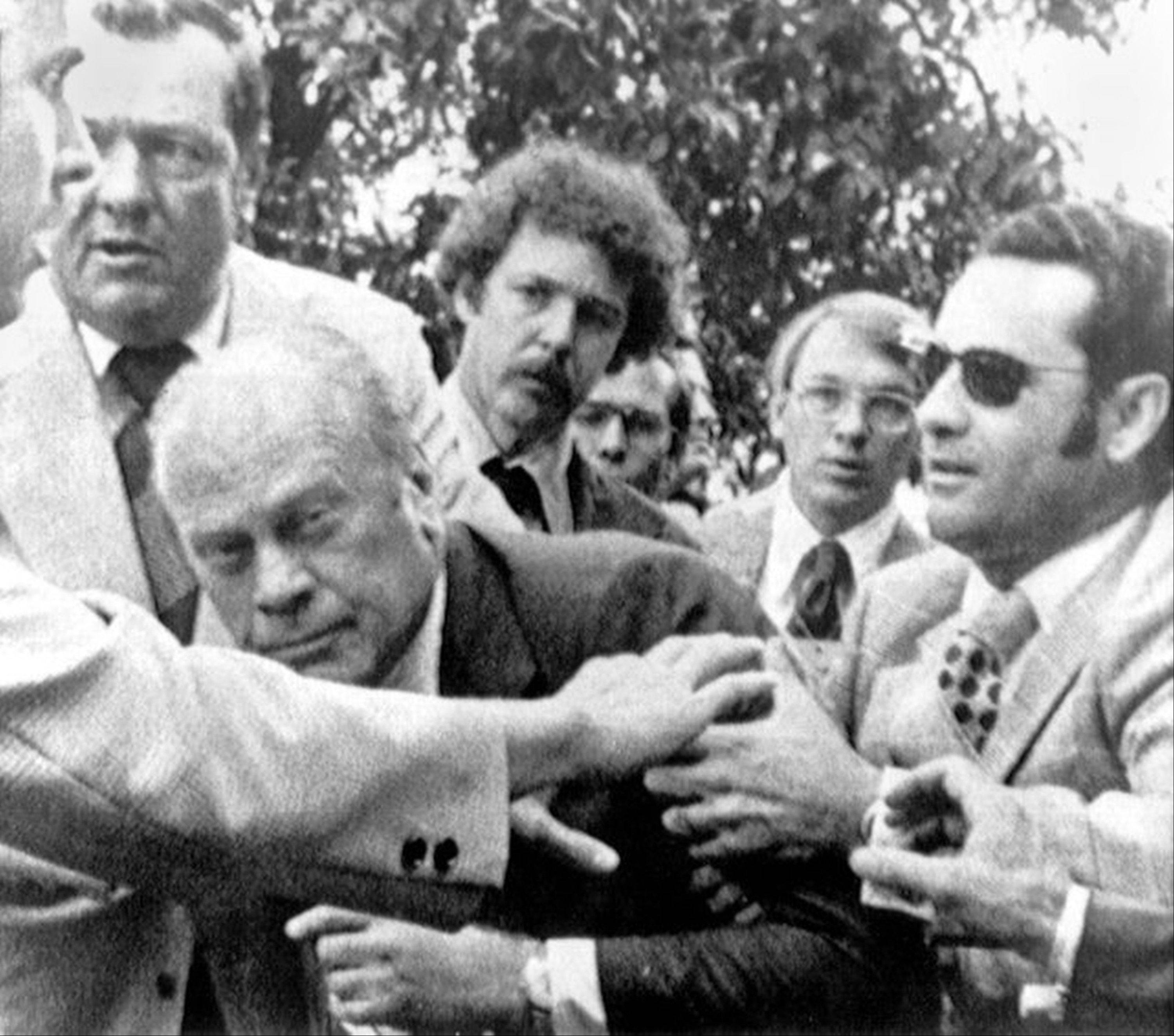 "President Gerald Ford is shielded by the Secret Service after an assassination attempt by Lynette ""Squeaky"" Fromme. President Ford had spoken at a ""Host Breakfast,"" and was walking to California's state Capitol in Sacramento, Calif. Almost 38 years after the assassination attempt, a federal judge has allowed the release of a videotaped testimony given by Ford, that was later used in Fromme's trial. Fromme, a devoted follower of the infamous Charles Manson, wearing a red robe, stepped out from behind a tree and pointed a loaded pistol at the President."