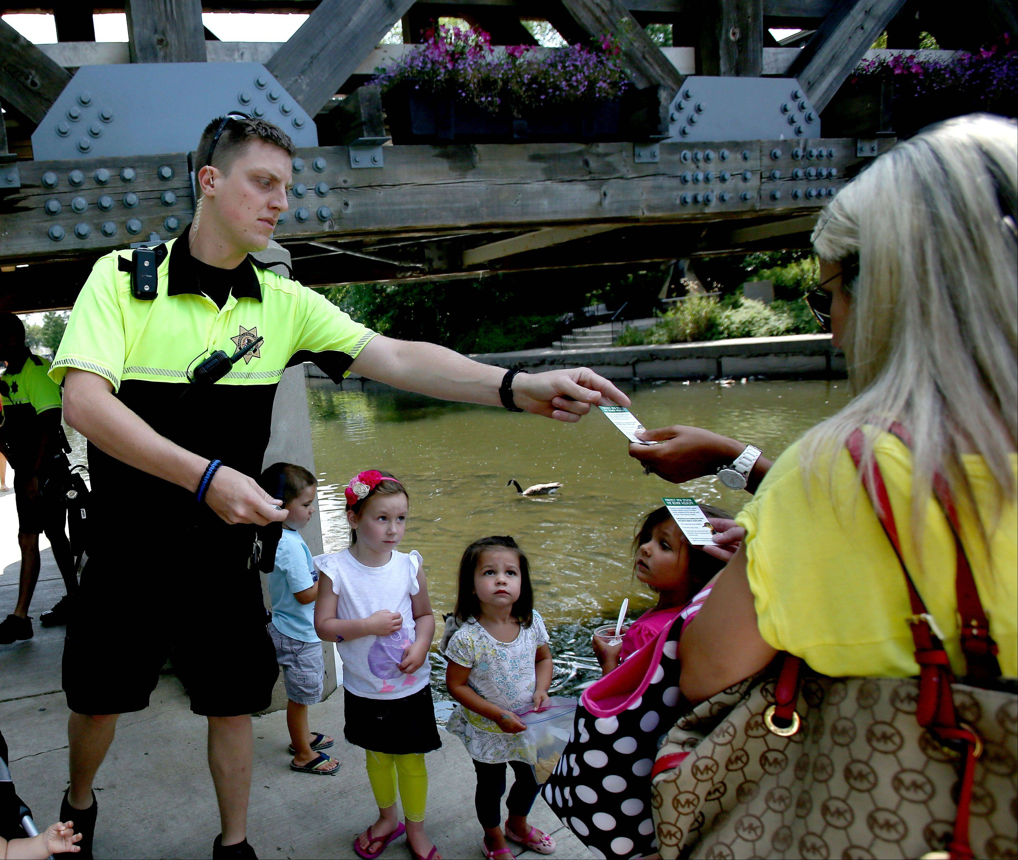 Naperville Park District police officers are handing out cards urging visitors not to feed the ducks or geese along the Riverwalk.