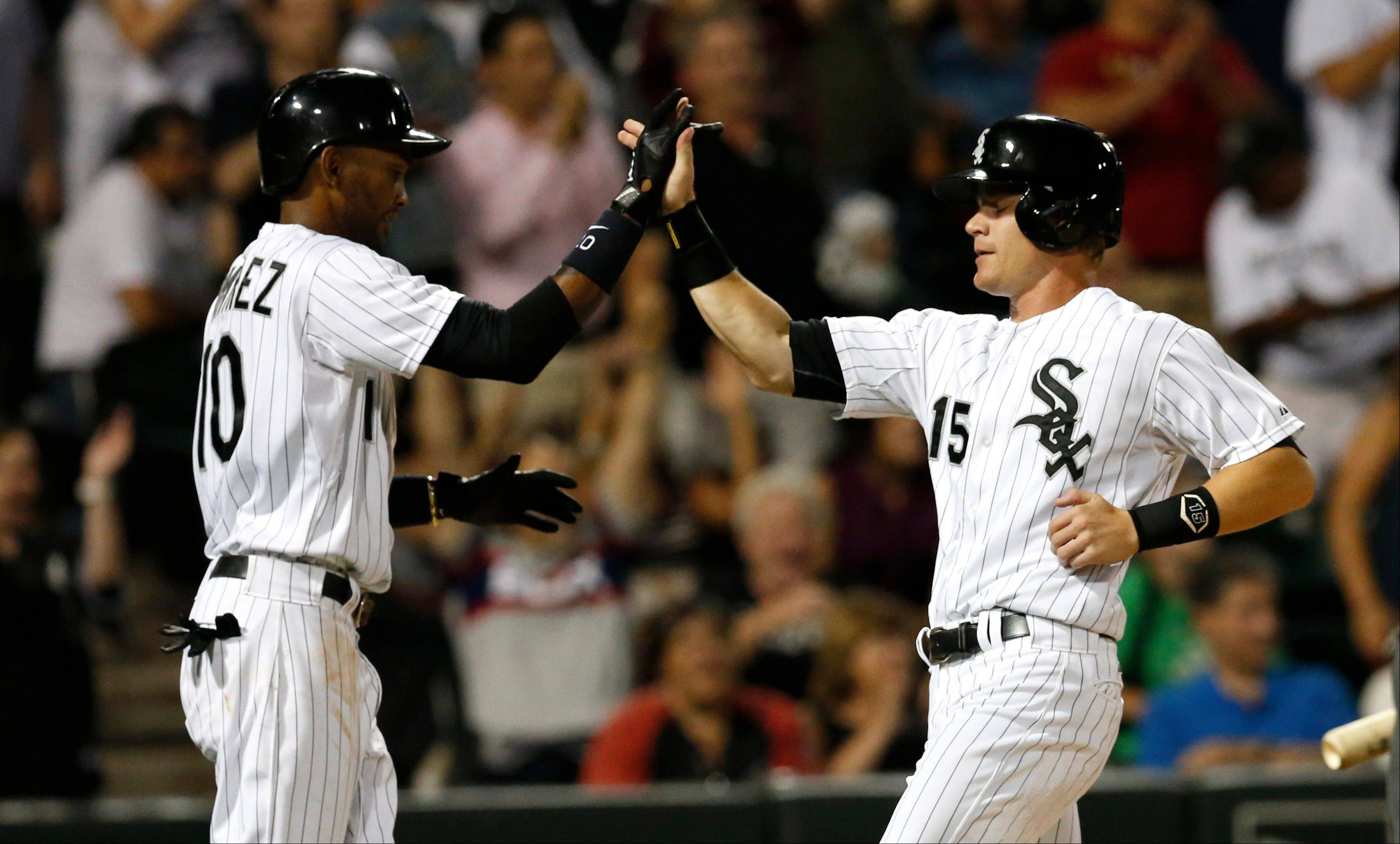 Alexei Ramirez, right, greets Gordon Beckham at home after the pair scored on a RBI single by Jordan Danks during the eighth inning of a baseball game against the Houston Astros, Tuesday, Aug. 27, 2013, in Chicago. (AP Photo/Charles Rex Arbogast)