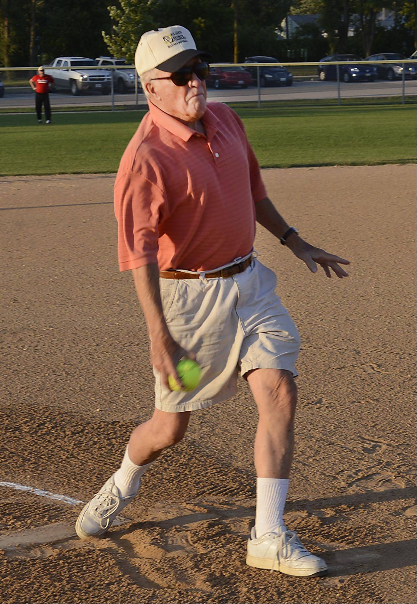 Bud Wilson throws the ceremonial first pitch Tuesday to start the Elgin Masters Softball League playoff tournament. He was honored with a trophy to thank him for keeping the league together since starting it in 1984.