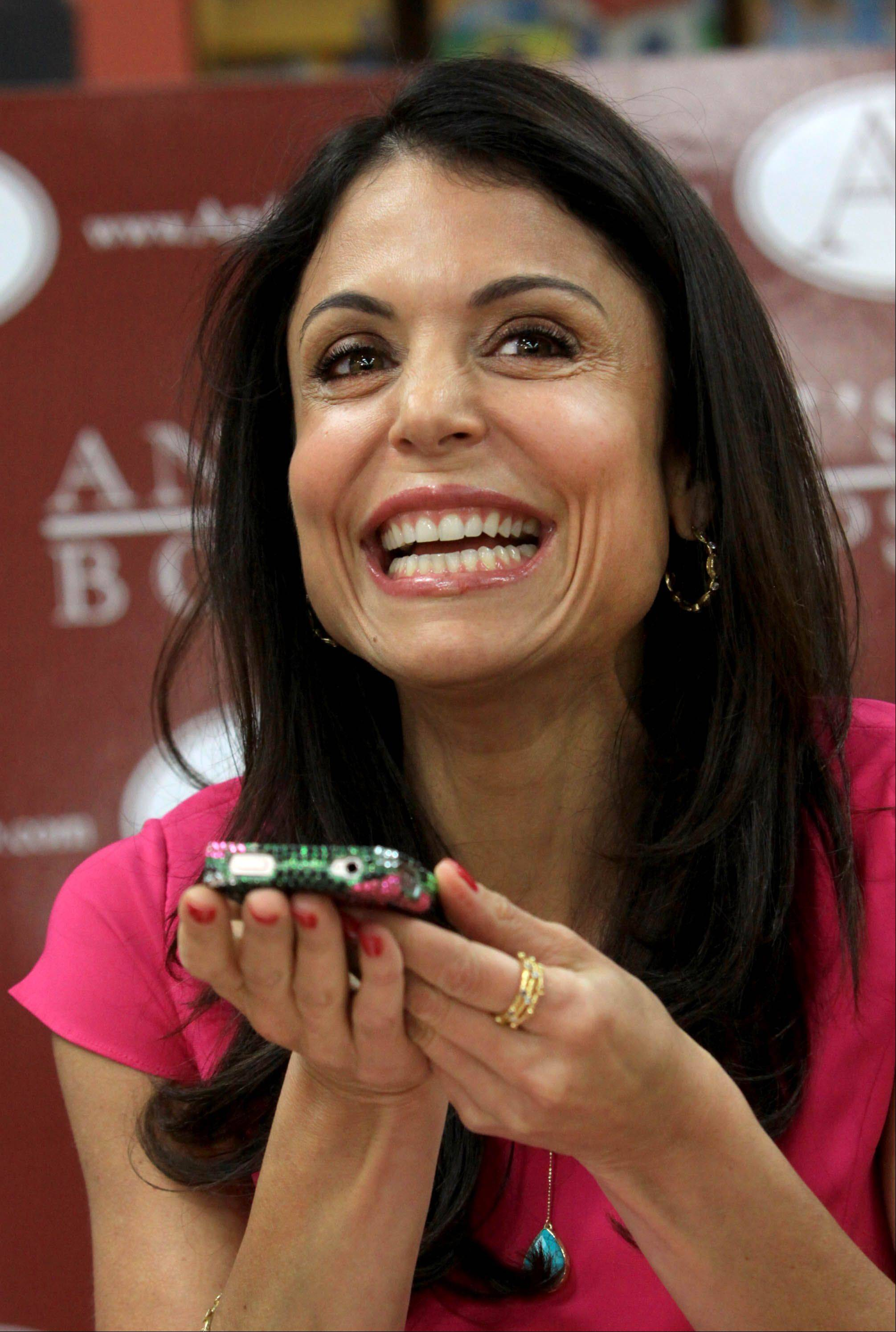 "Bethenny Frankel, talk show host and creator of the Skinnygirl brand of cocktails, beauty and health products, makes a call on speakerphone Tuesday to a friend of Jen Evers of Naperville, who won a trip to New York for the filming of Frankel's show ""bethenny."""