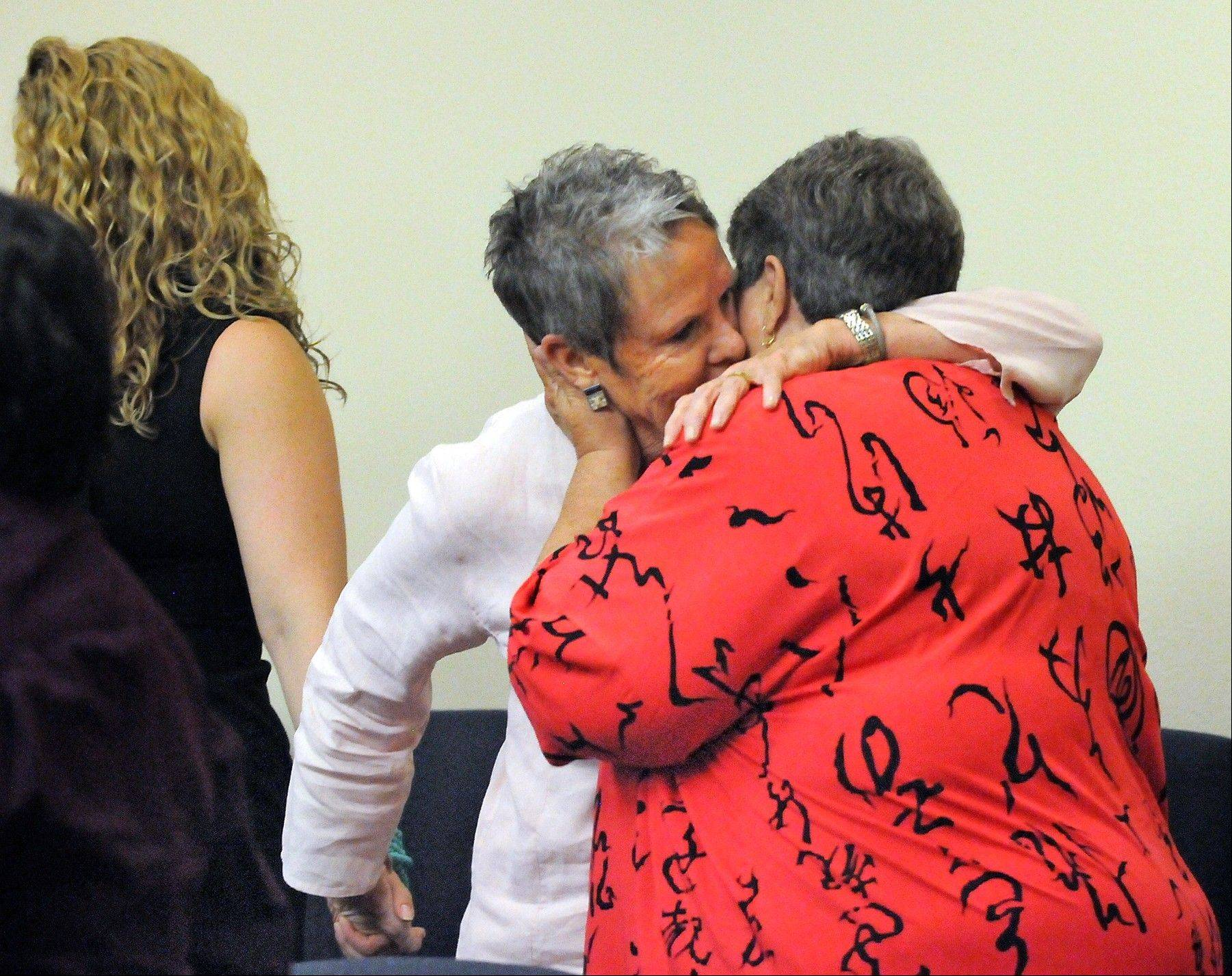 Ona Porter, center, gives her partner Miriam Rand, right, a hug while holding the hand of their daughter Emilie Porter-Rand, left, Monday Aug. 26, 2013, after Judge Alan M. Malott made his ruling on licenses for same sex couples in Bernalillo County, N.M.