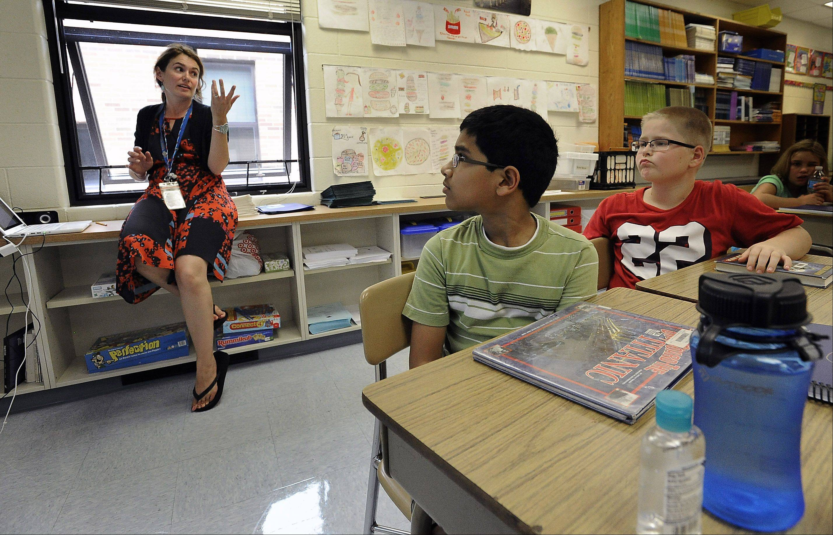 Fourth-grade teacher Lisa Moore sweats it out with students Sai Tarra and Ihor Nychay and the rest of her classroom without air conditioning Monday at Mark Twain Elementary School in Wheeling.