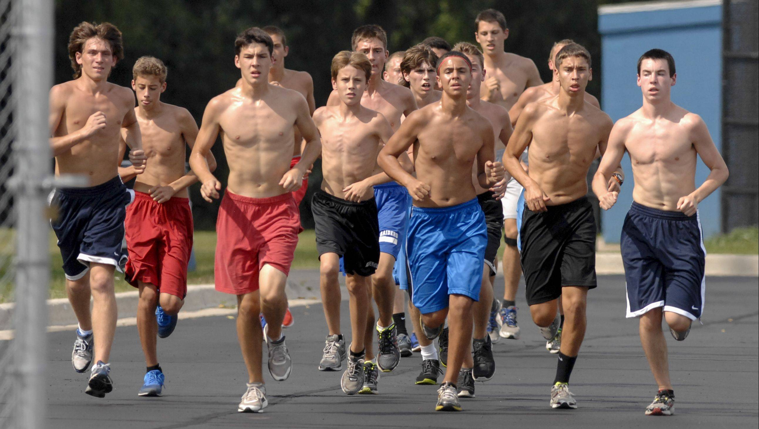 Glenbard South High School varsity cross country runners practice without shirts Monday to help deal with the heat.