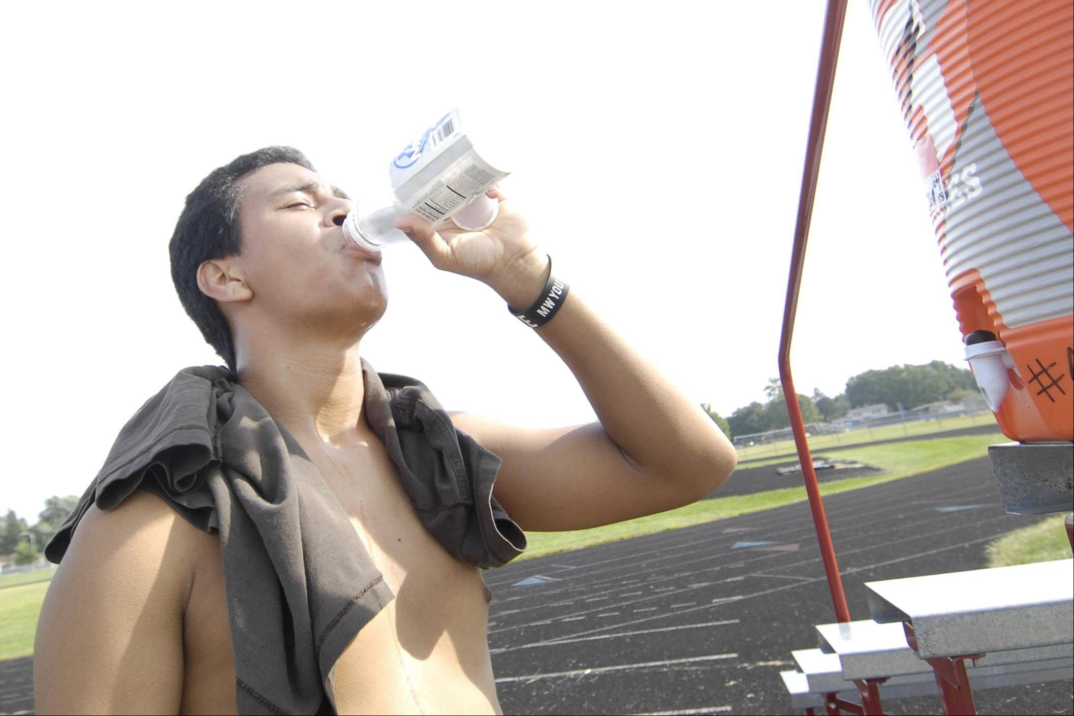Alberto Velazquez, a Larkin High School senior, gets water at the end of cross country practice Monday. The team ran a one-mile time trial in the heat.