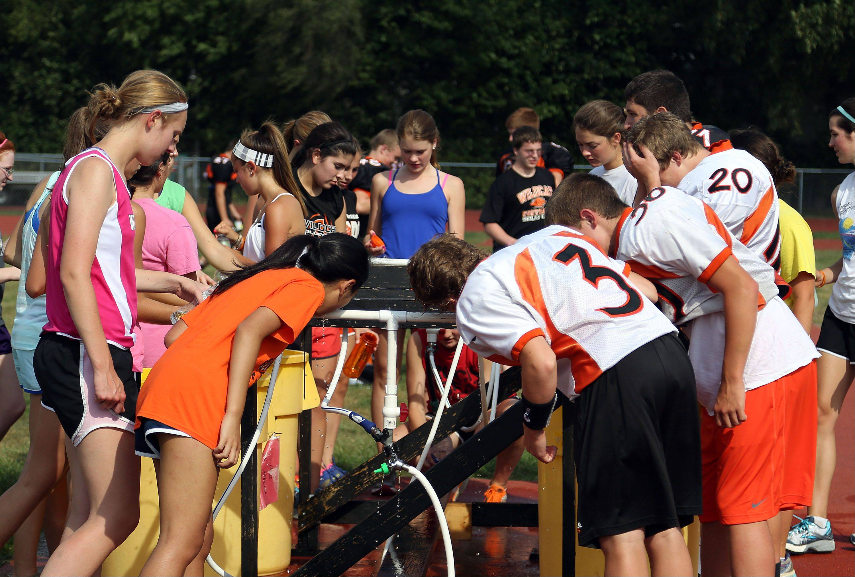 Cross country and football players share a watering station as temperatures got into the 90's Monday at Libertyville High School.