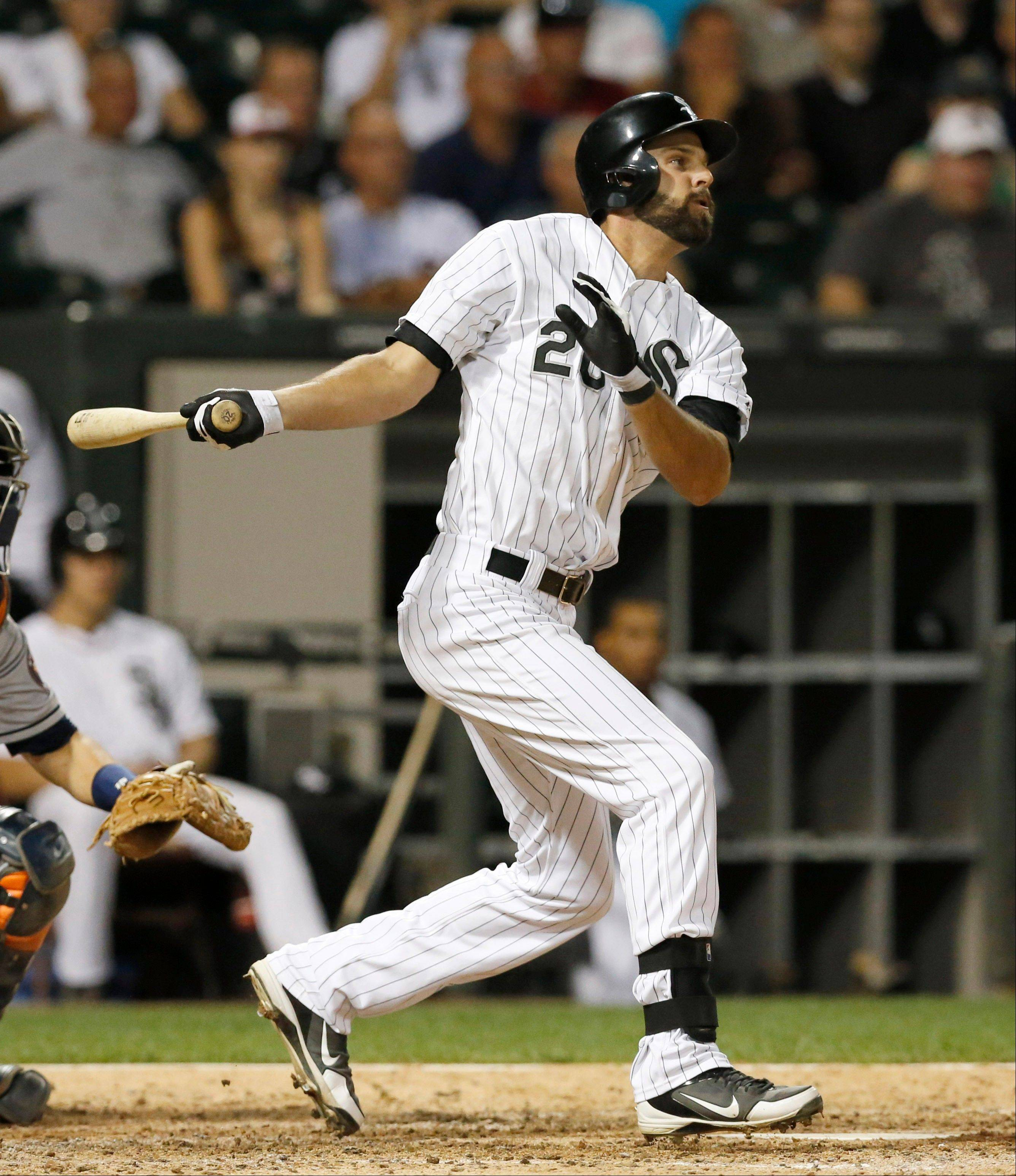 White Sox's Jordan Danks hits a two-run single off Houston Astros relief pitcher Erik Bedard, scoring Alexei Ramirez and Gordon Beckham, during the eighth inning of a baseball game Tuesday, Aug. 27, 2013, in Chicago.