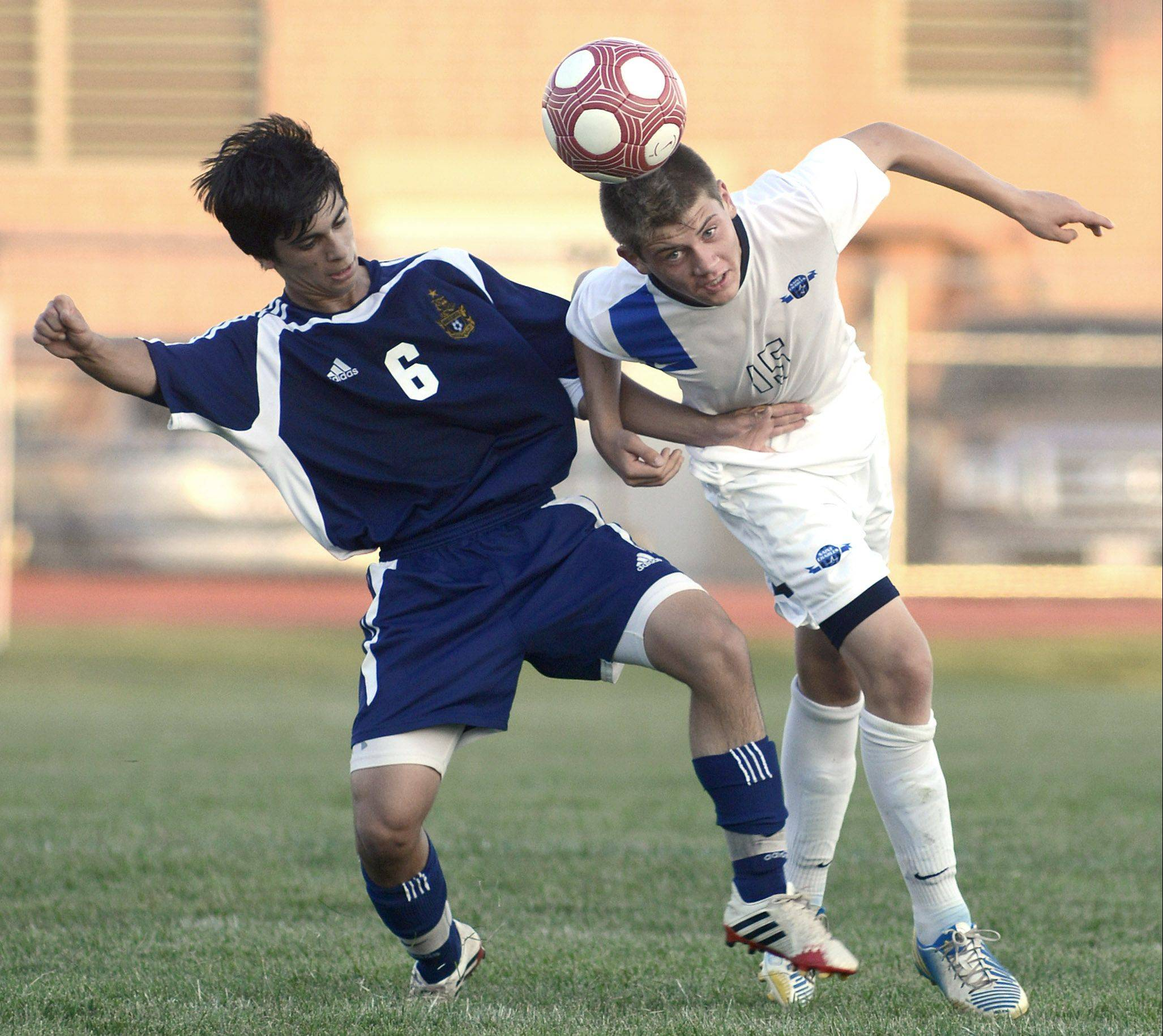 St. Charles North's Ryan Olson heads the ball against Neuqua Valley's Kas Baladi on Tuesday in St. Charles.