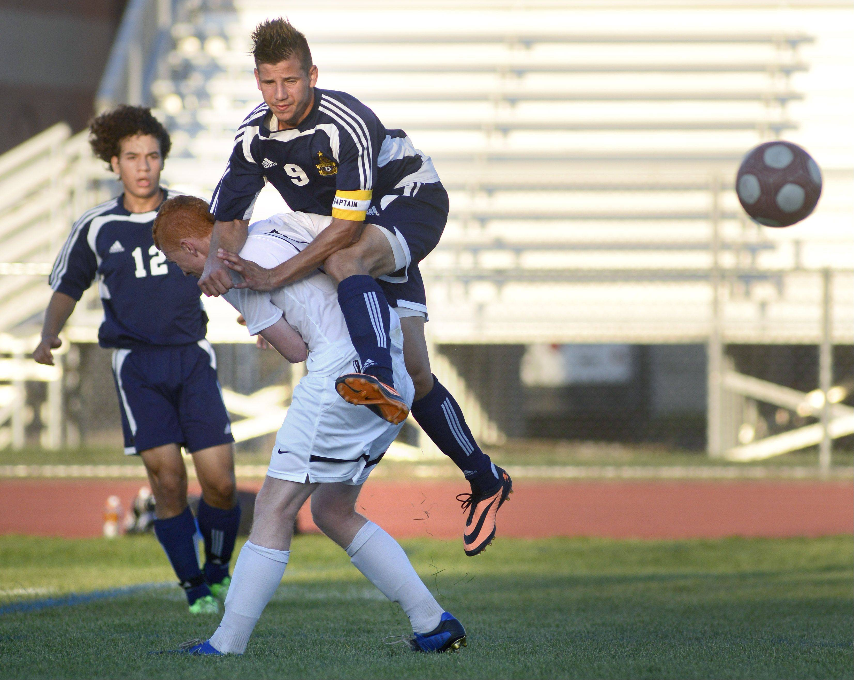 Neuqua Valley's Jake Loncar leaps onto the back of St. Charles North's Jack Fries after deflecting the ball in the first half on Tuesday, August 27.