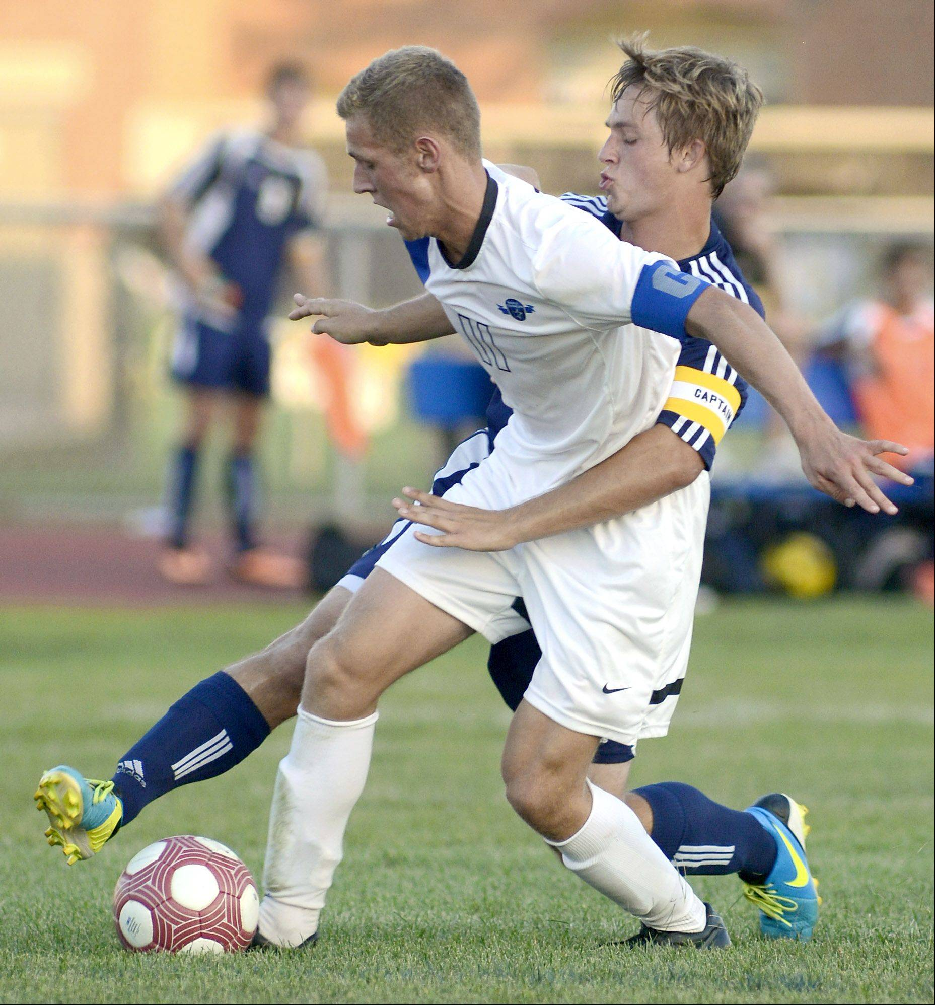 St. Charles North's Phillip LeGare and Neuqua Valley's Nick Castelvecchi wrestle for possession of the ball in the first half on Tuesday, August 27.
