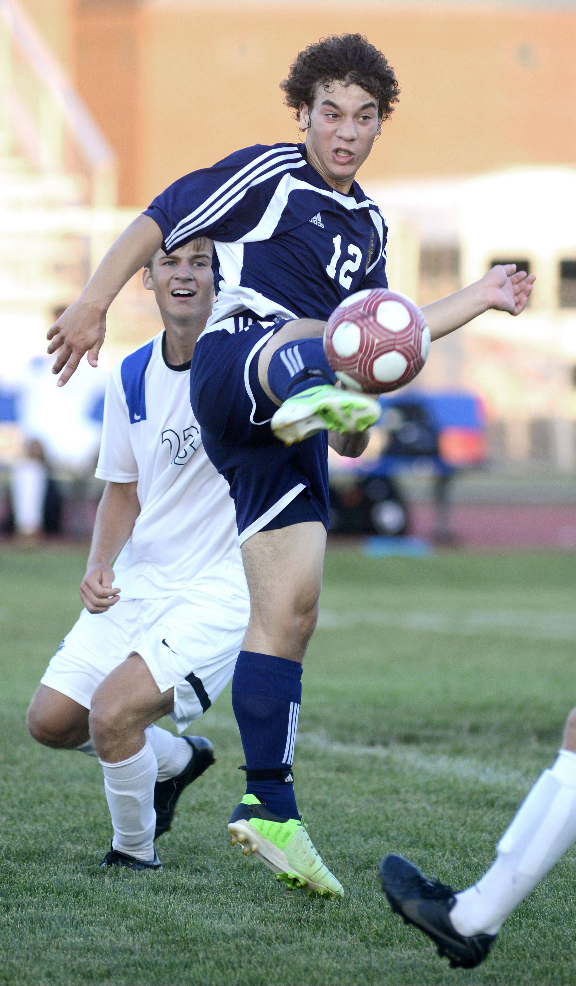 Neuqua Valley's Kersey Dickerson redirects the ball with a high kick with St. Charles North's Adam Hoffman on his back in the first half on Tuesday, August 27.