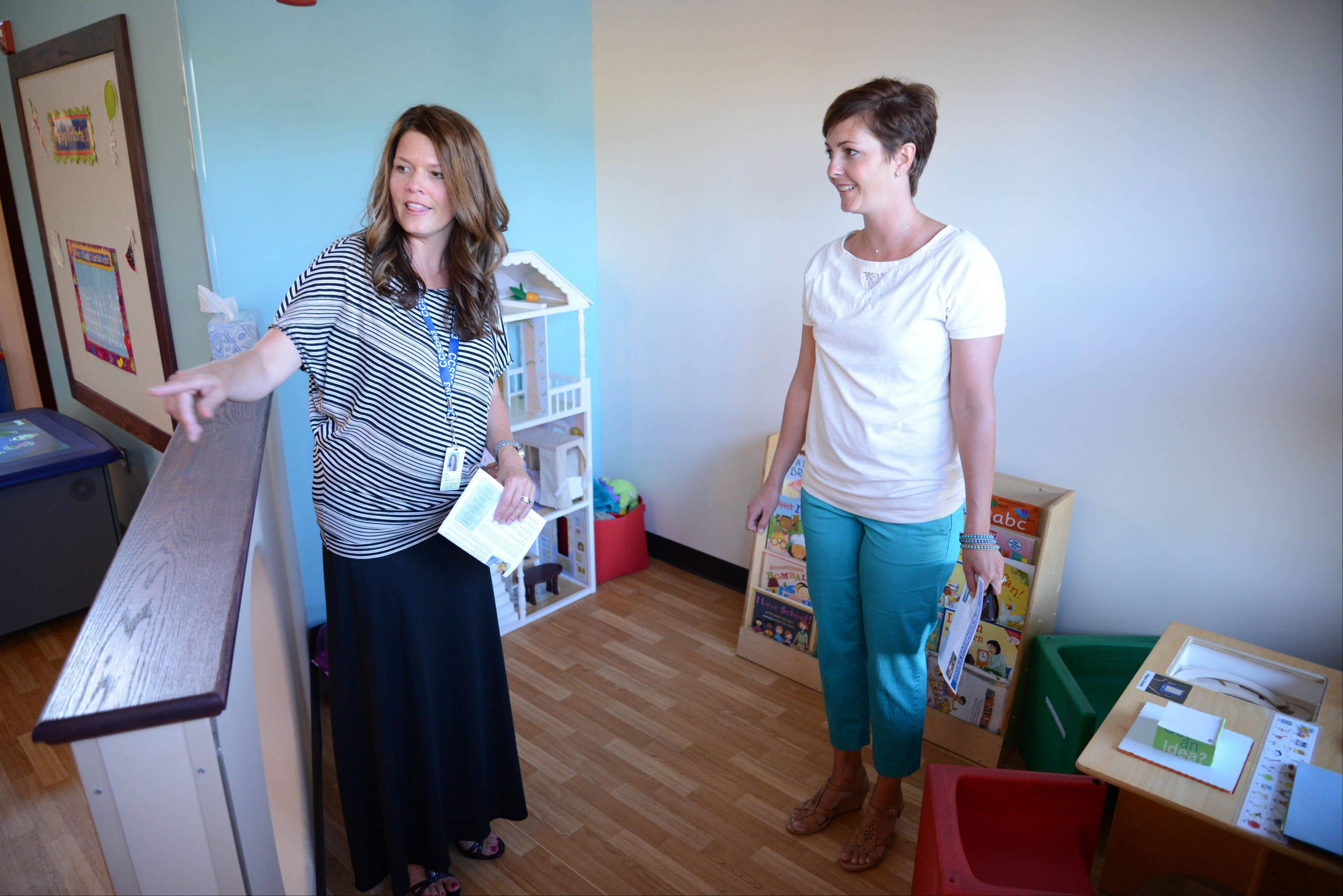 Teacher Lisa Lally, left, shows Nichole Palumbo of Carol Stream a classroom at the new District 93 Early Childhood Center Tuesday night. The first day of school is Thursday.