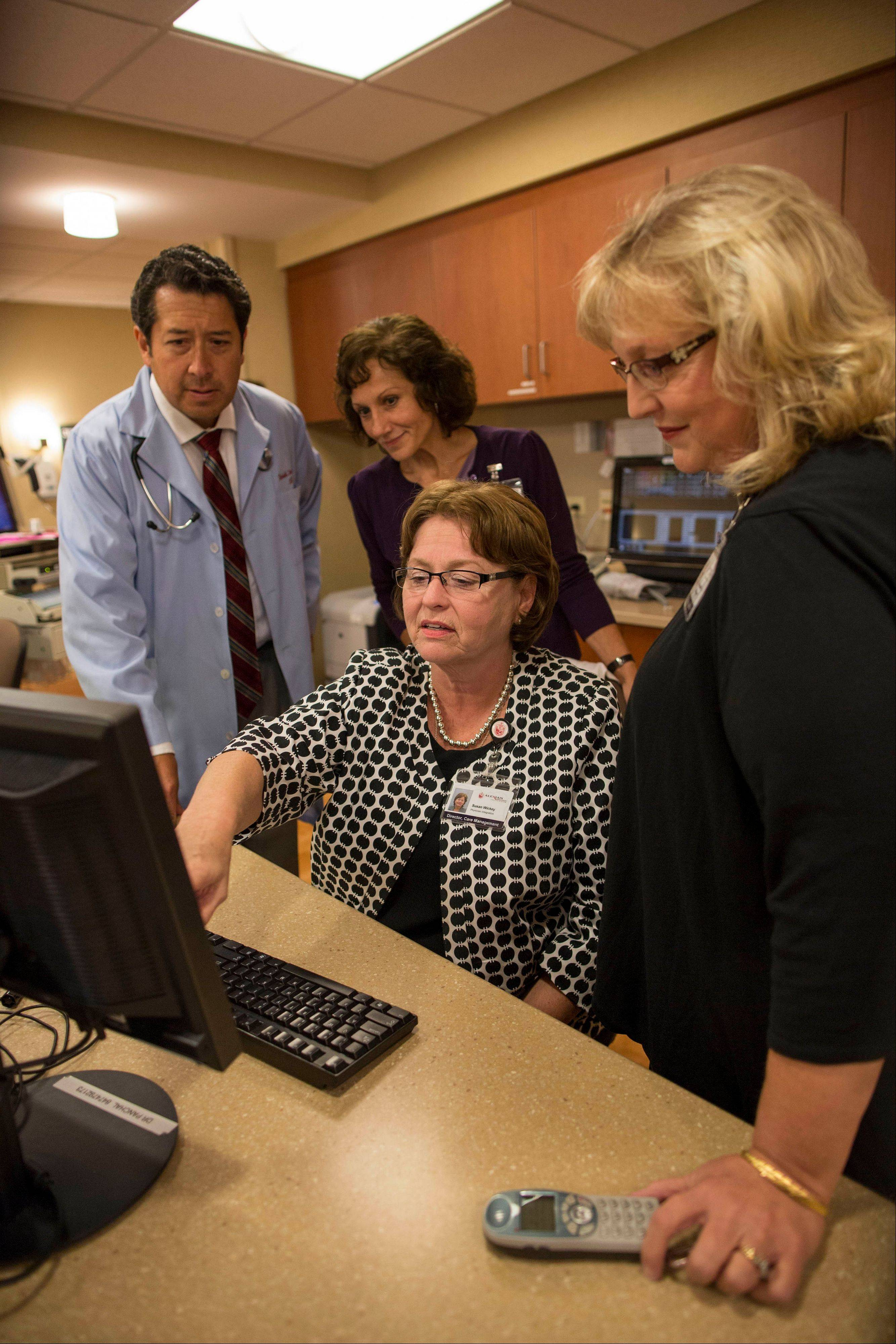 Dr. Reinhold Illerna, from left, administrative director of case management, Mary Schumann, director of care management, Sue Wickey and Jolene Grabowski, social work manager, work on a computer at a nurses station at the Alexian Brothers Medical Center in Elk Grove Village.