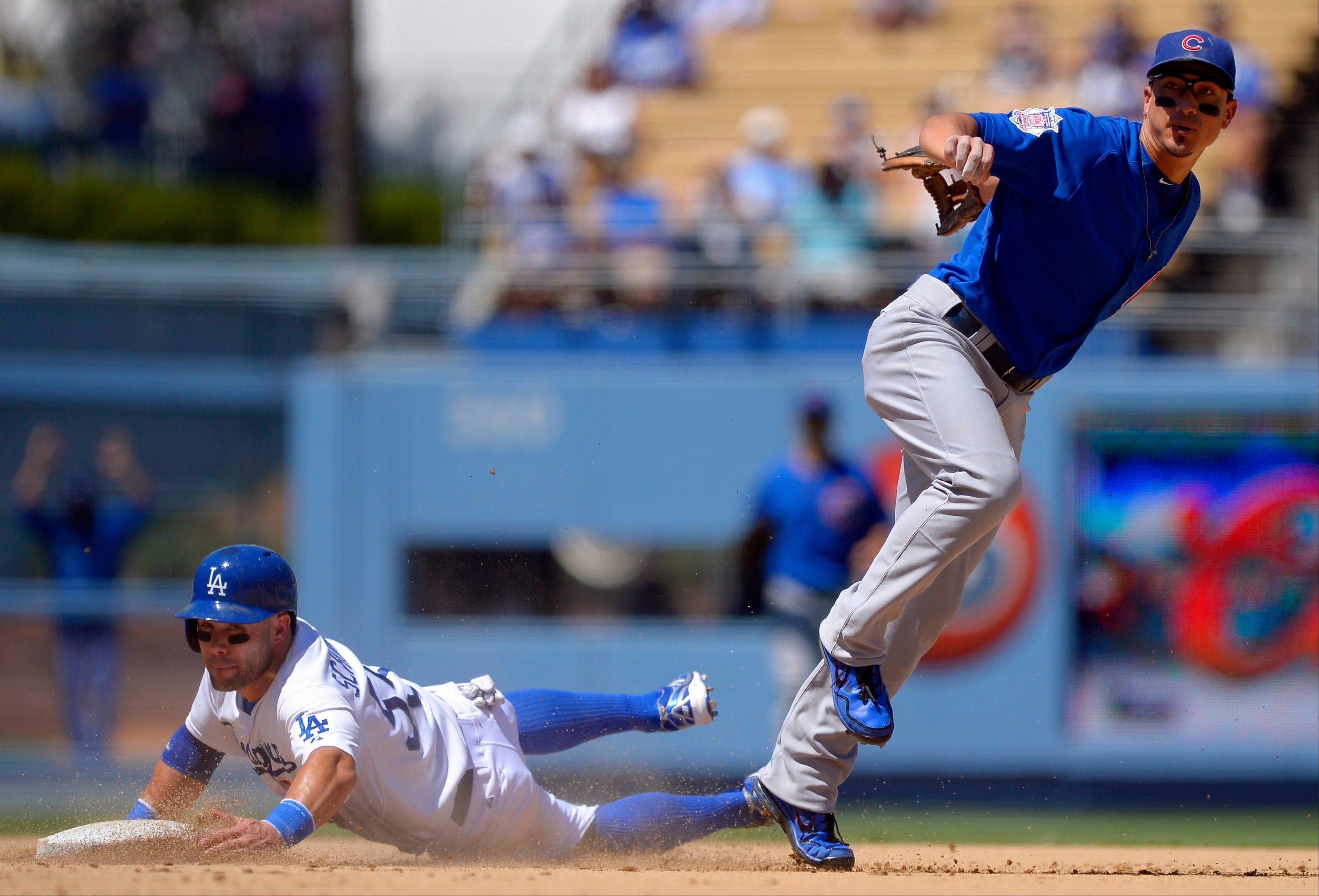 The Dodgers� Skip Schumaker, left, is forced out at second as Chicago Cubs second baseman Darwin Barney attempts to throw out Hanley Ramirez at first during Wednesday�s game in Los Angeles. The Cubs lost 4-0.