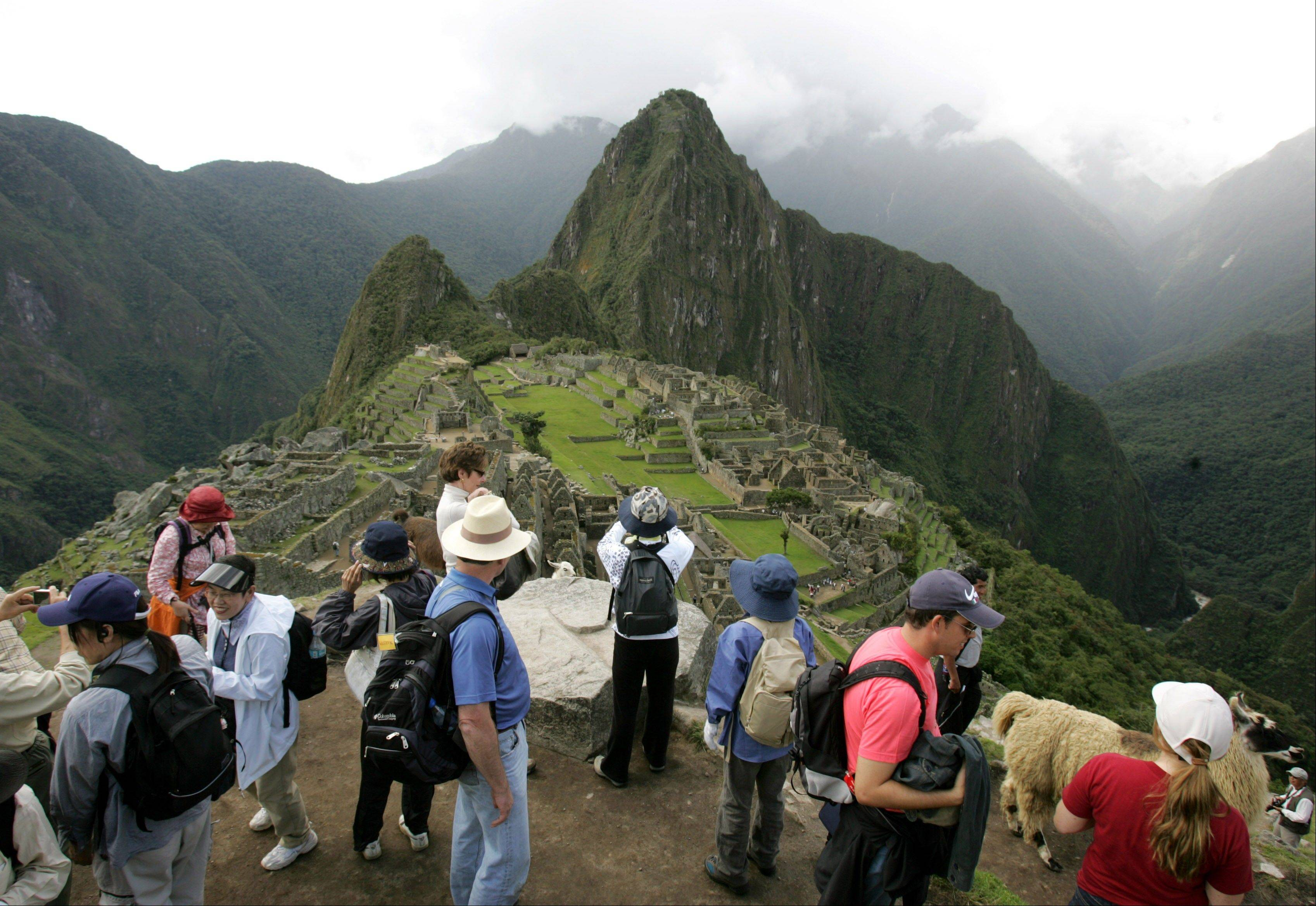 Tourists look at the Inca citadel of Machu Picchu in Peru. The government is looking to shift some of the tourist burden from Machu Picchu, to Choquequirao, with a plan to build the first aerial tramway that will make Choquequirao reachable in just 15 minutes from the nearest highway.