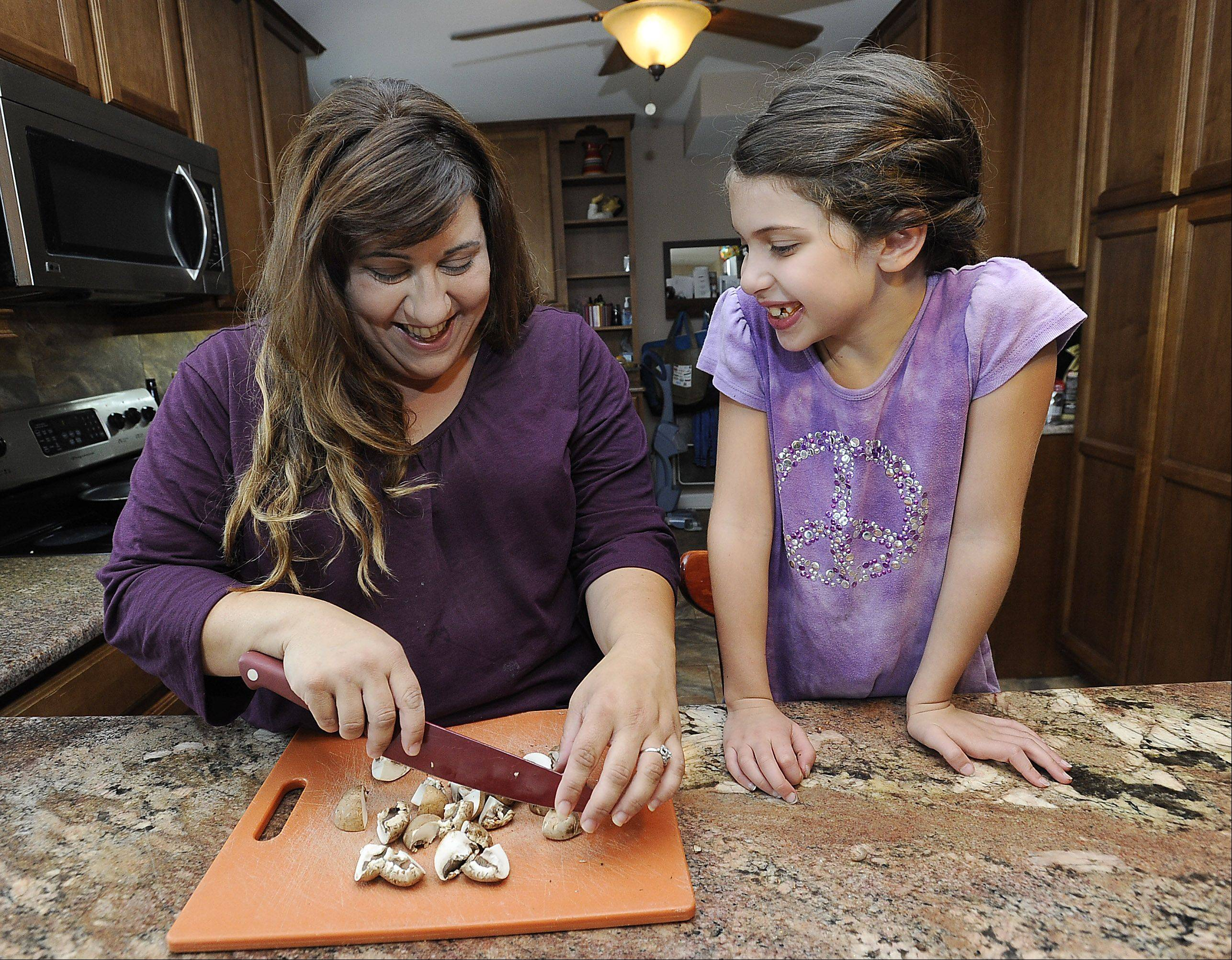 Mark Welsh/mwelsh@dailyherald.comTina Garrett of DesPlaines in her kitchen with her daughter Lillian,7, chopping up mushrooms for her next food dish.