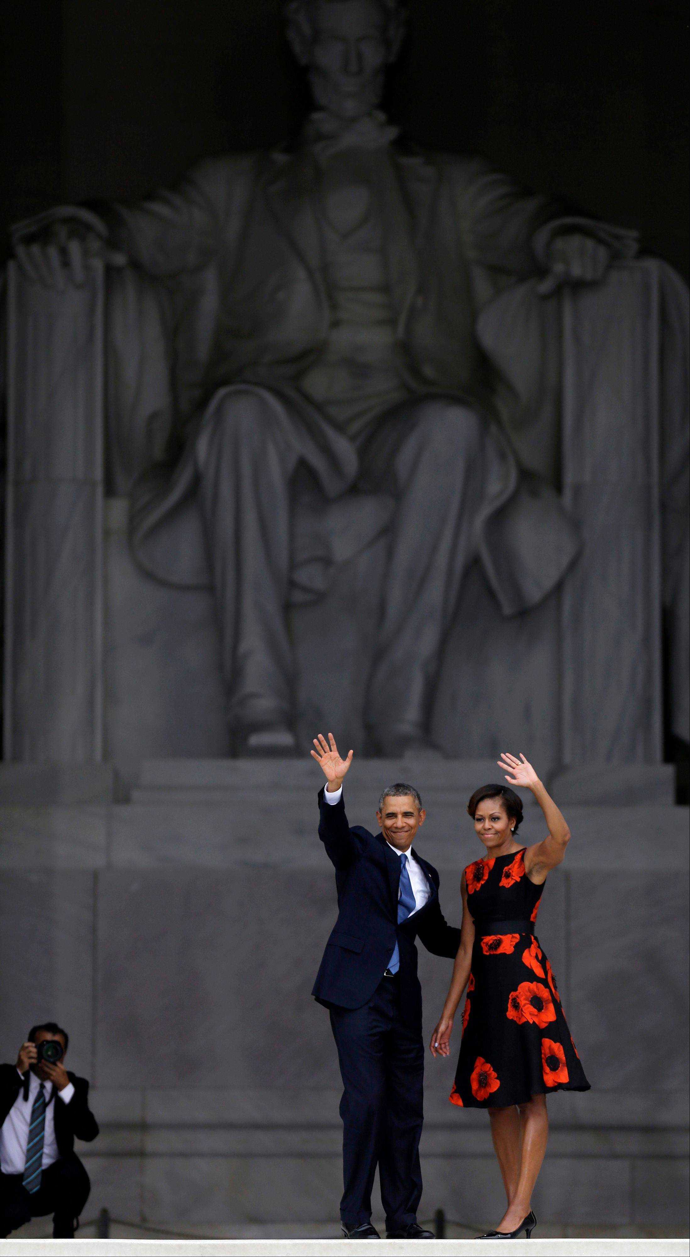 President Barack Obama and first lady Michelle Obama wave to the crowd from the steps of the Lincoln Memorial at the conclusion of the the Let Freedom Ring ceremony.
