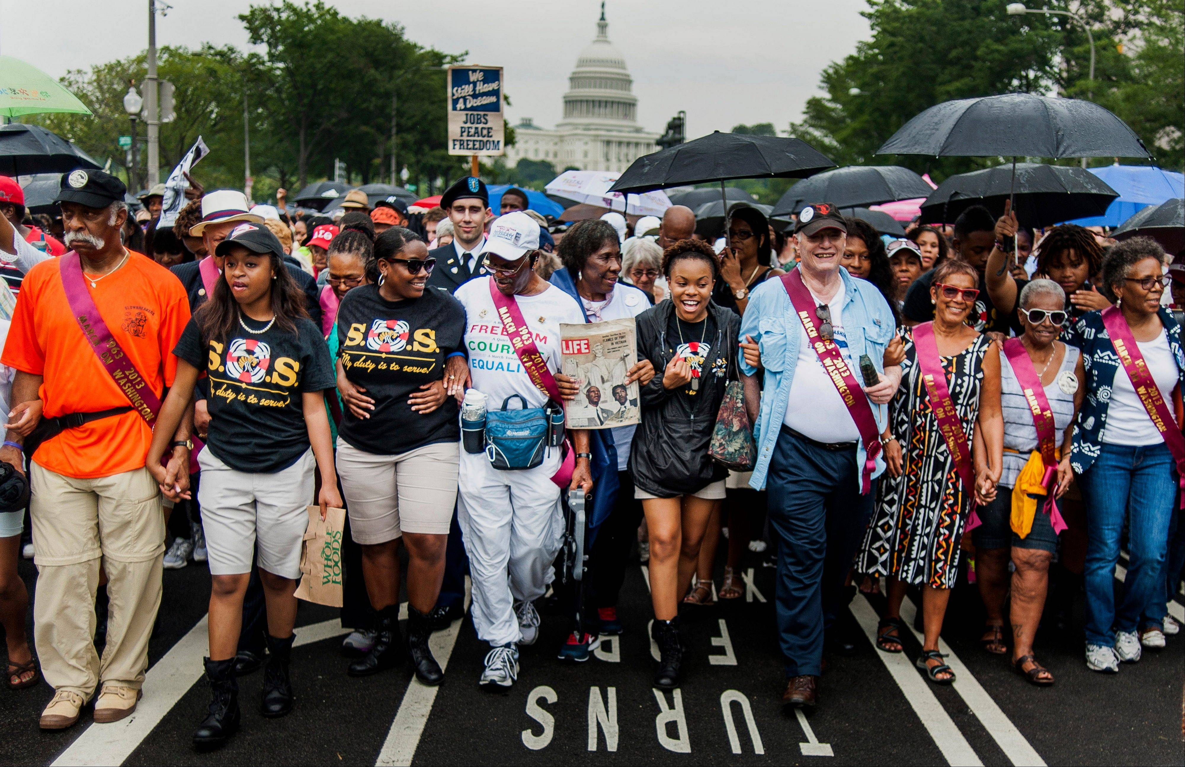 Participants walk in the March for Jobs and Justice in Washington, D.C., U.S., on Wednesday, Aug. 28, 2013. The march was part of the Let Freedom Ring ceremony.