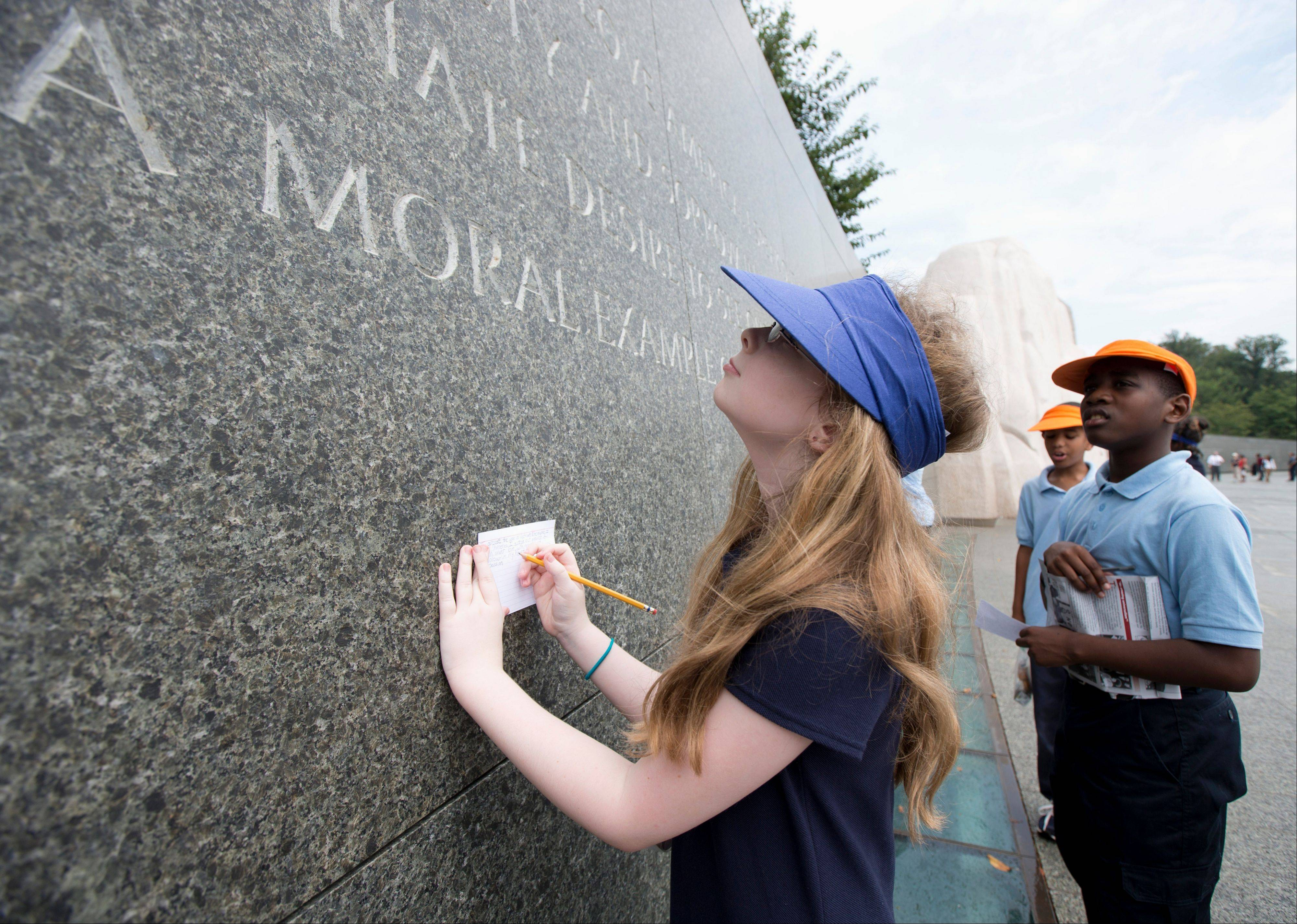 Brianna Renner, 11, left, and Morgan Koroma, 11, both from Cora Rich Elementary School in Prince Georges County, Md., read and write down quotes from Martin Luther King's speeches and writings, inscribed on the wall at the Martin Luther King Memorial in Washington.