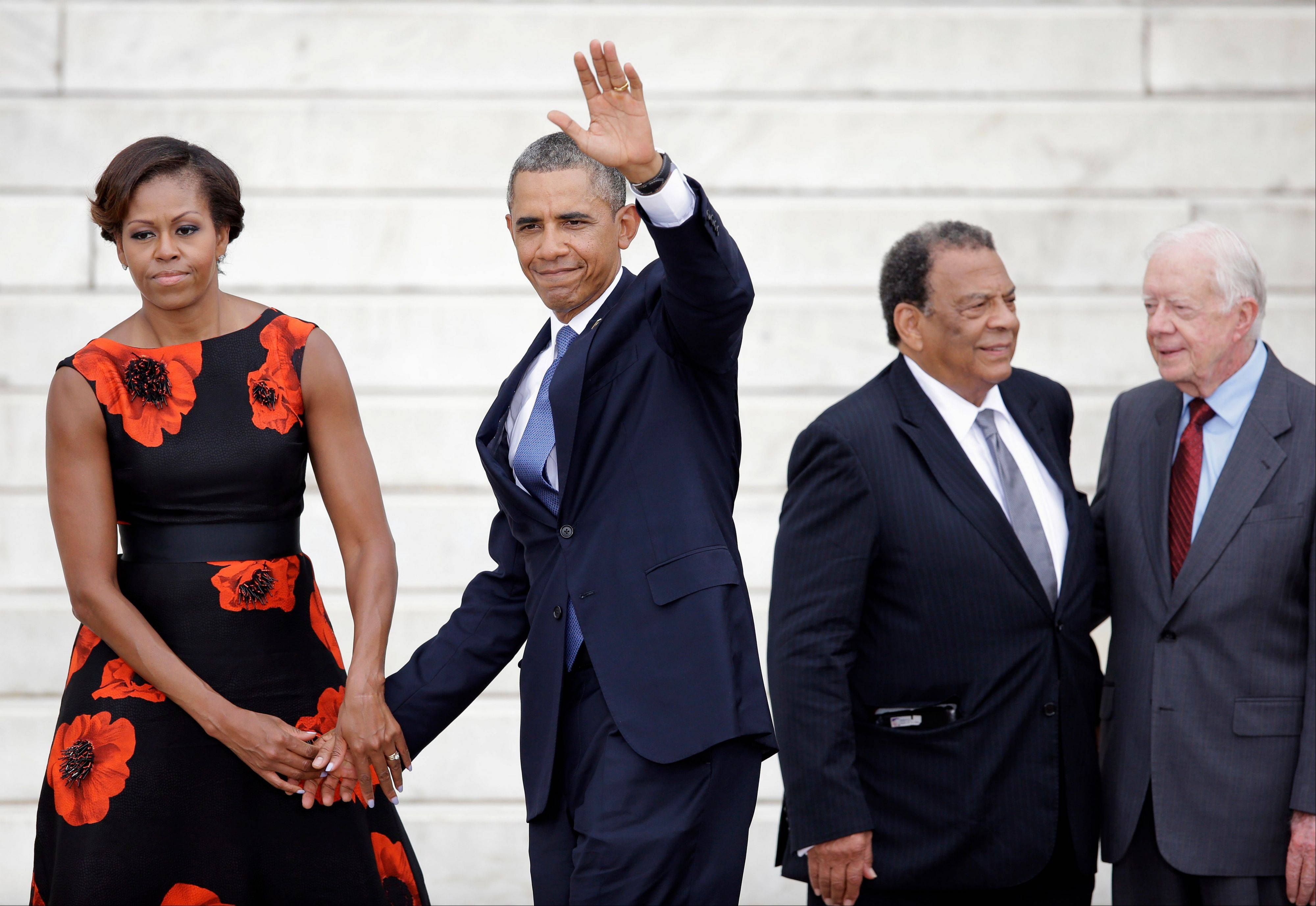 President Barack Obama, accompanied by first lady Michelle Obama, waves at the Let Freedom Ring ceremony at the Lincoln Memorial in Washington.