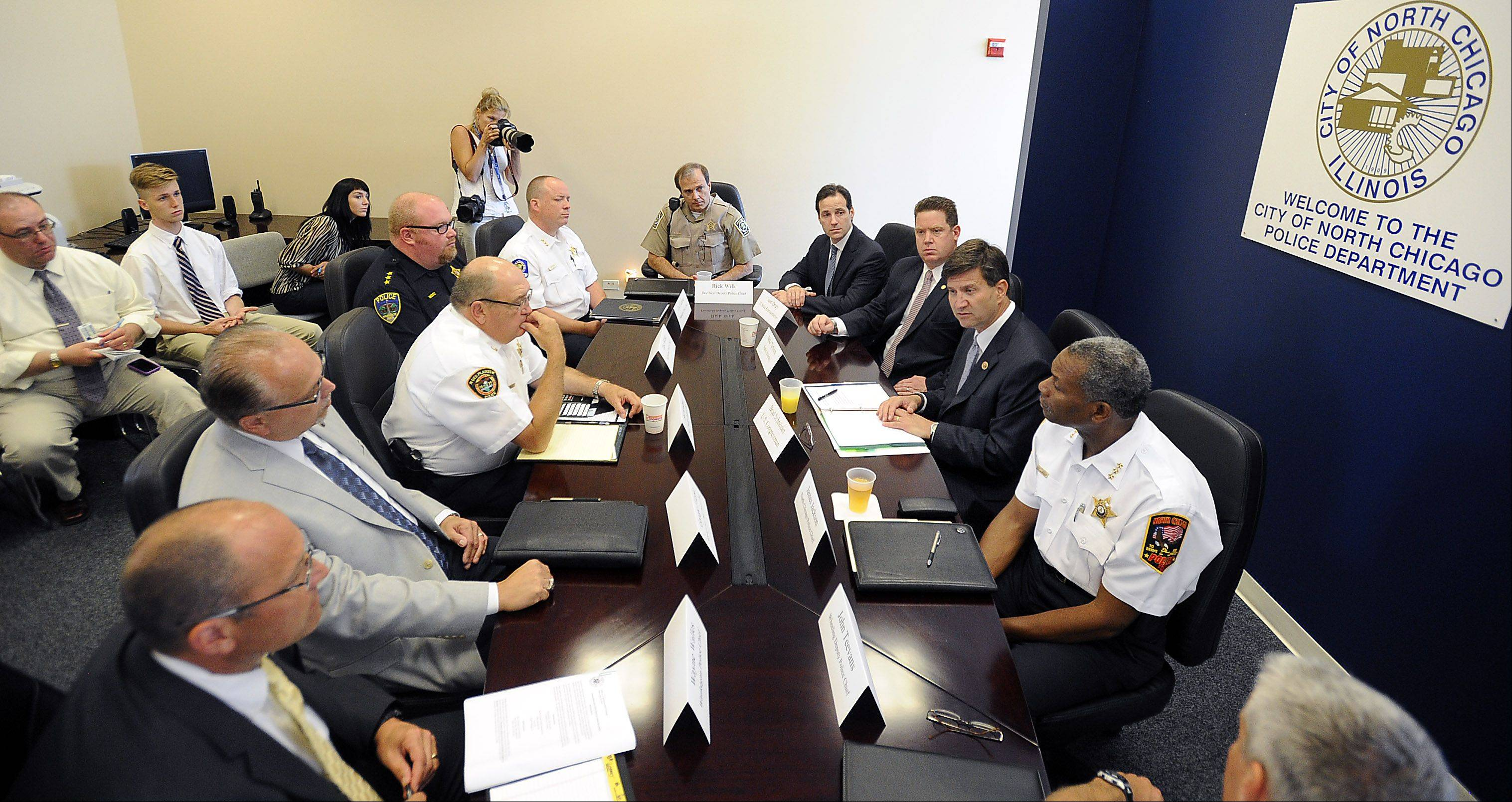 U.S. 10th District congressman Brad Schneider, center/right, talks with North Chicago Police Chief James Jackson, right, and other area police chiefs about ways to combat gun violence on local, federal and state levels in North Chicago on Wednesday.