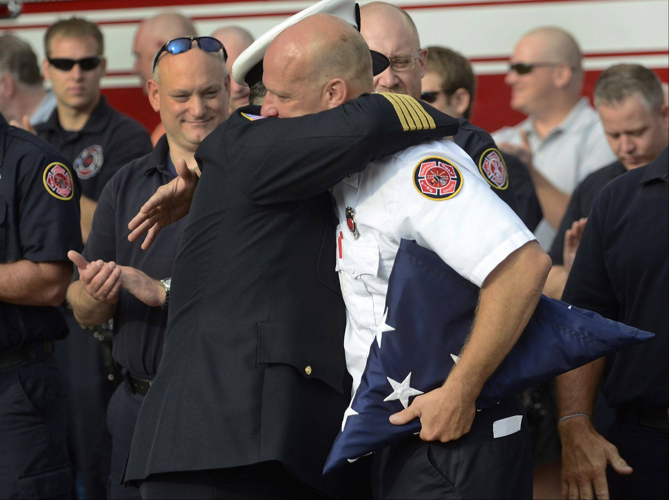 "Buffalo Grove Fire Lt. William ""Kent"" Brecht, right, is hugged by Chief Terry Vavra after receiving the station flag on the occasion of his retirement after 25 years with the department."