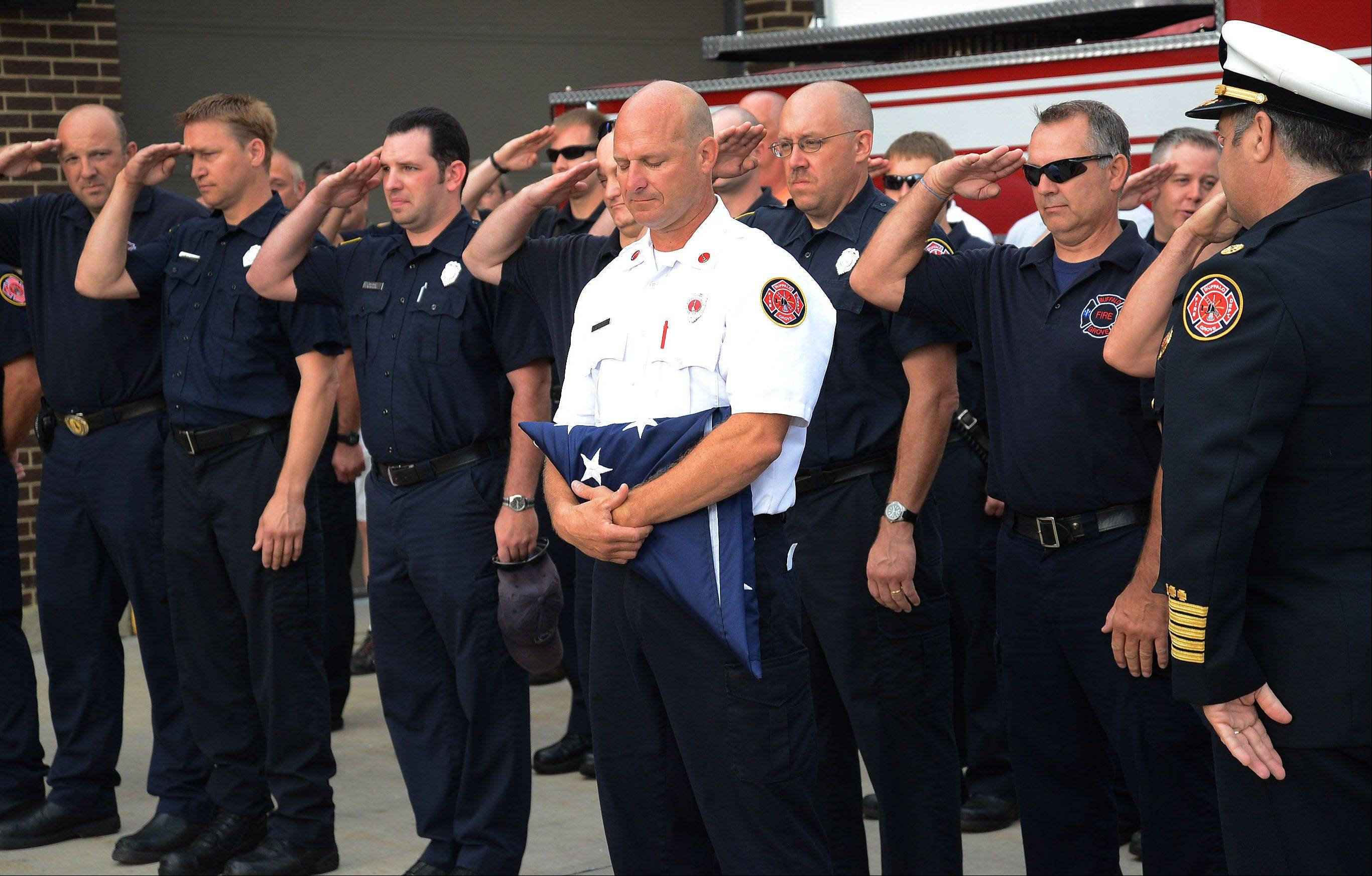 "Buffalo Grove Fire Lt. William ""Kent"" Brecht is saluted by the department after receiving the station flag on the occasion of his retirement after 25 years with the department."