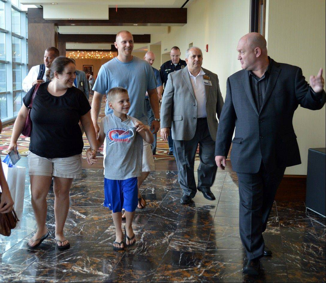 Michigan City Mayor Ron Meer, far right, and Jack Elia of Blue Chip Casino, second from right, welcome 6-year-old Nathan Woessner, center, and his parents, Faith, left, and Greg, behind Nathan, of Sterling, Ill., to the Blue Chip Casino in Michigan City, Ind. Tuesday afternoon. Michigan City is hosting a pair of events Wednesday to recognize those involved in rescuing Nathan, who was trapped beneath 11 feet of sand for more than three hours at Mount Baldy on July 12.