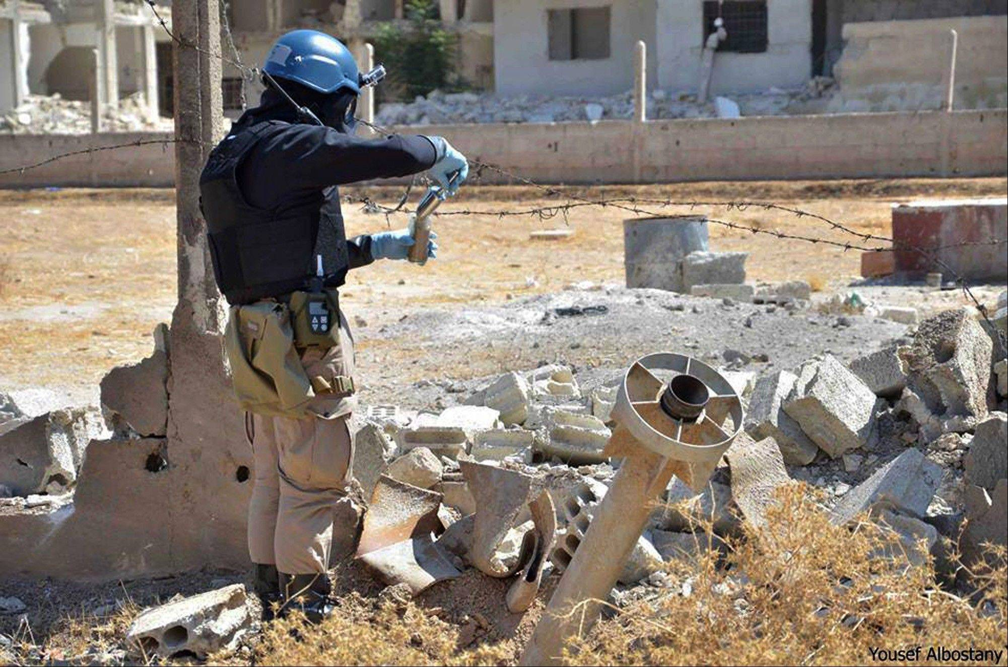 This image provided by the United Media Office of Arbeen shows a member of UN investigation team taking samples of sands near a part of a missile that could be one of the chemical rockets used in last week's suspected poison gas attack on Syrian civilians.