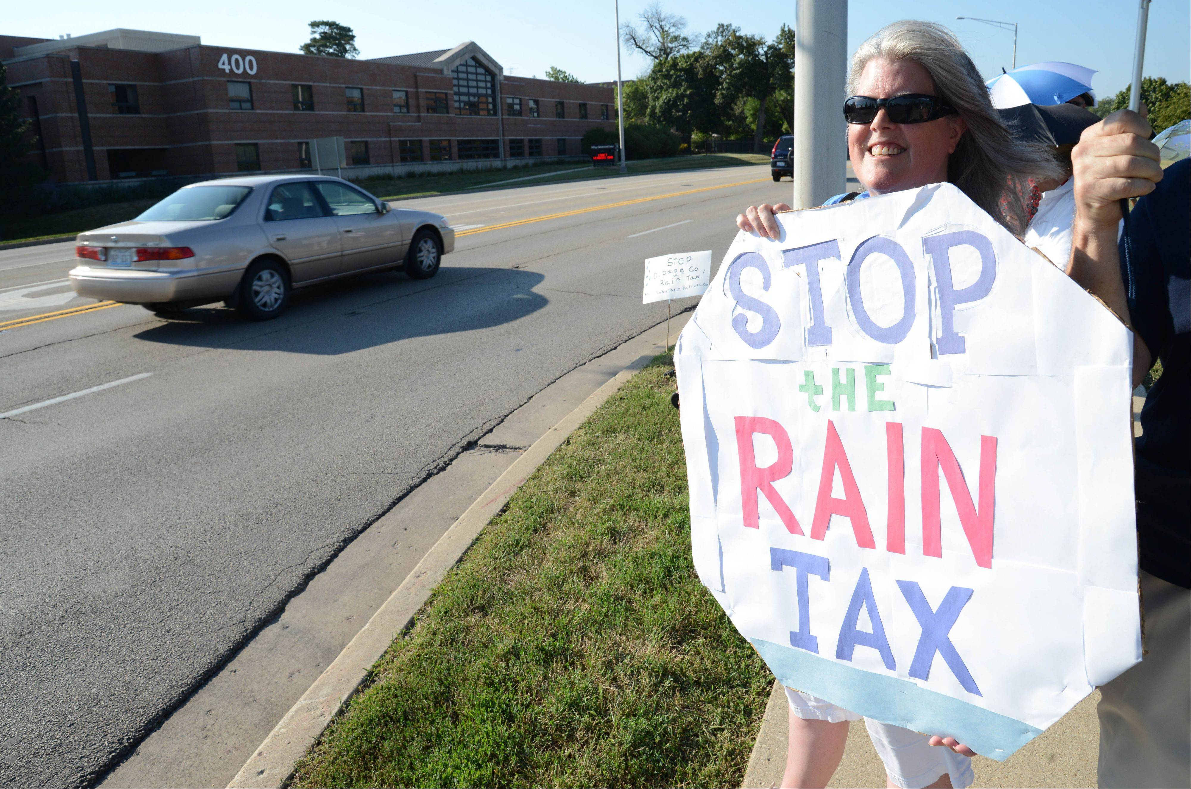 On Tuesday night, Janet Shaw of Wheaton and more than 30 other residents stood in front of DuPage County's administration building along County Farm Road to protest a new state law that gives DuPage the power to impose a stormwater fee on every land owner in the county.