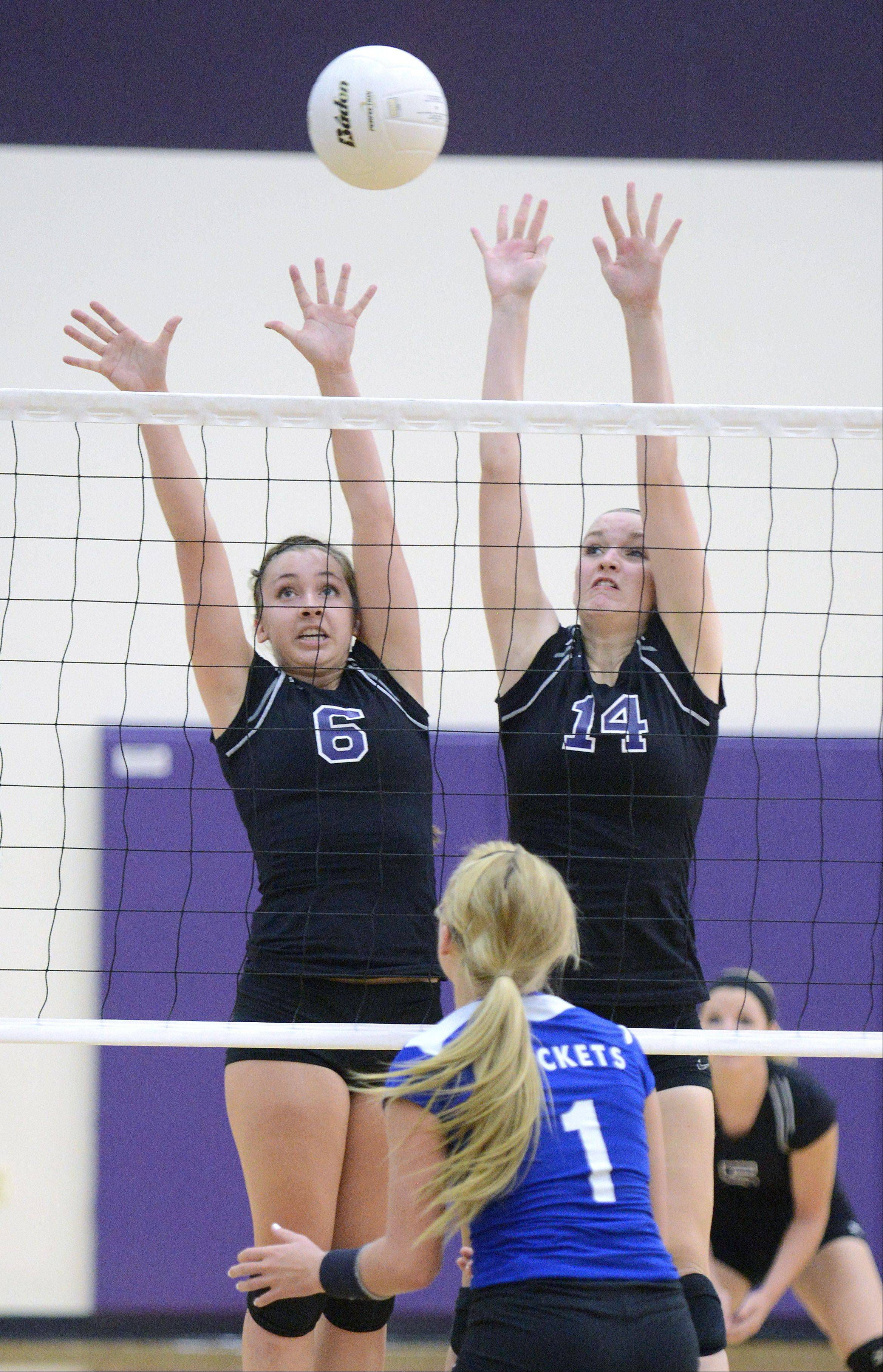 Hampshire's Brittany Laffin, left, and Sophia Robson block a spike by Burlington Central's Allie O'Reilly in game one on Wednesday, August 28.