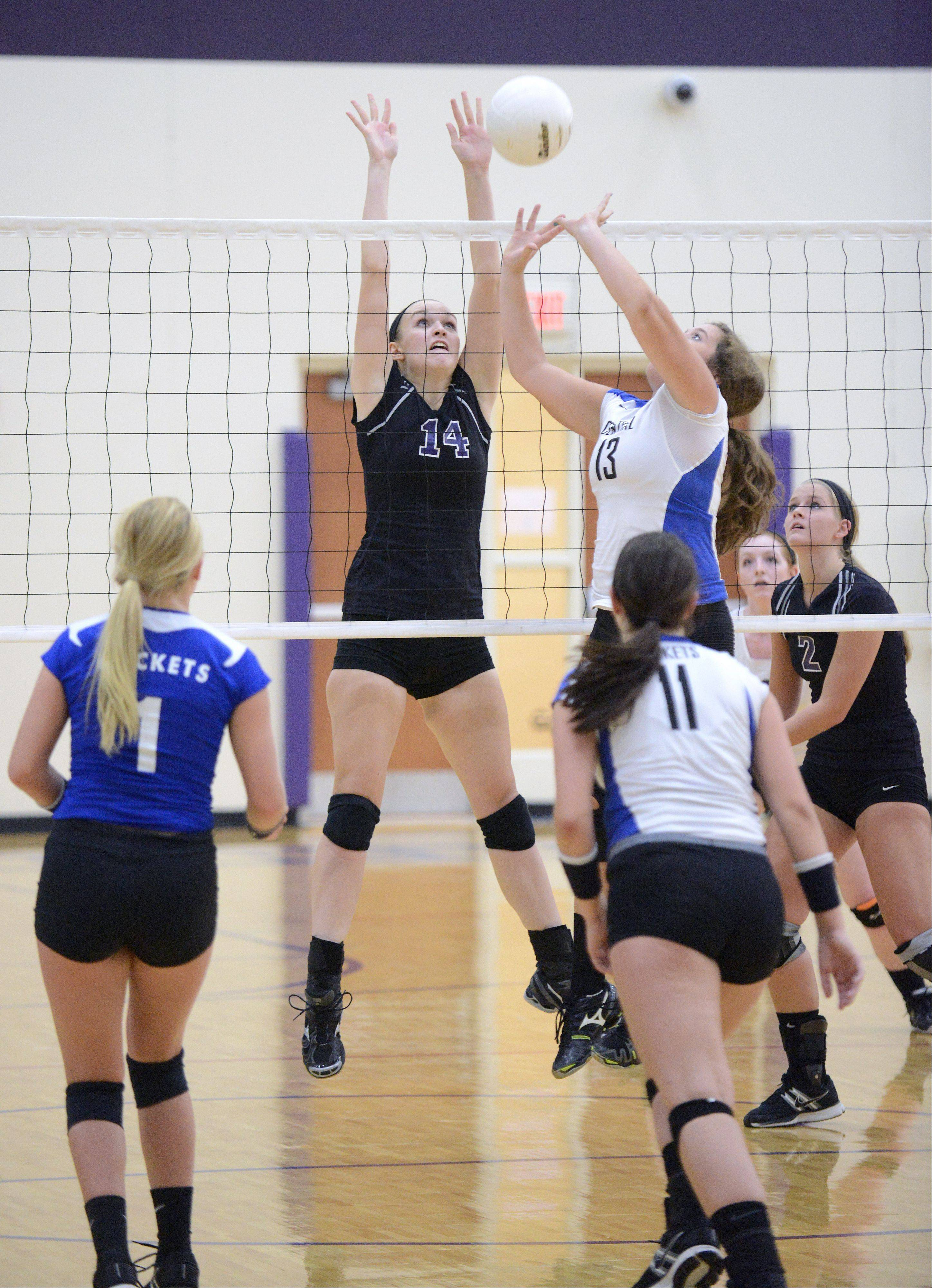 Burlington Central's Maddy Barry sets up a spike for teammate Allie O'Reilly as Hampshire's Sophia Robson leaps to block during game one on Wednesday, August 28.