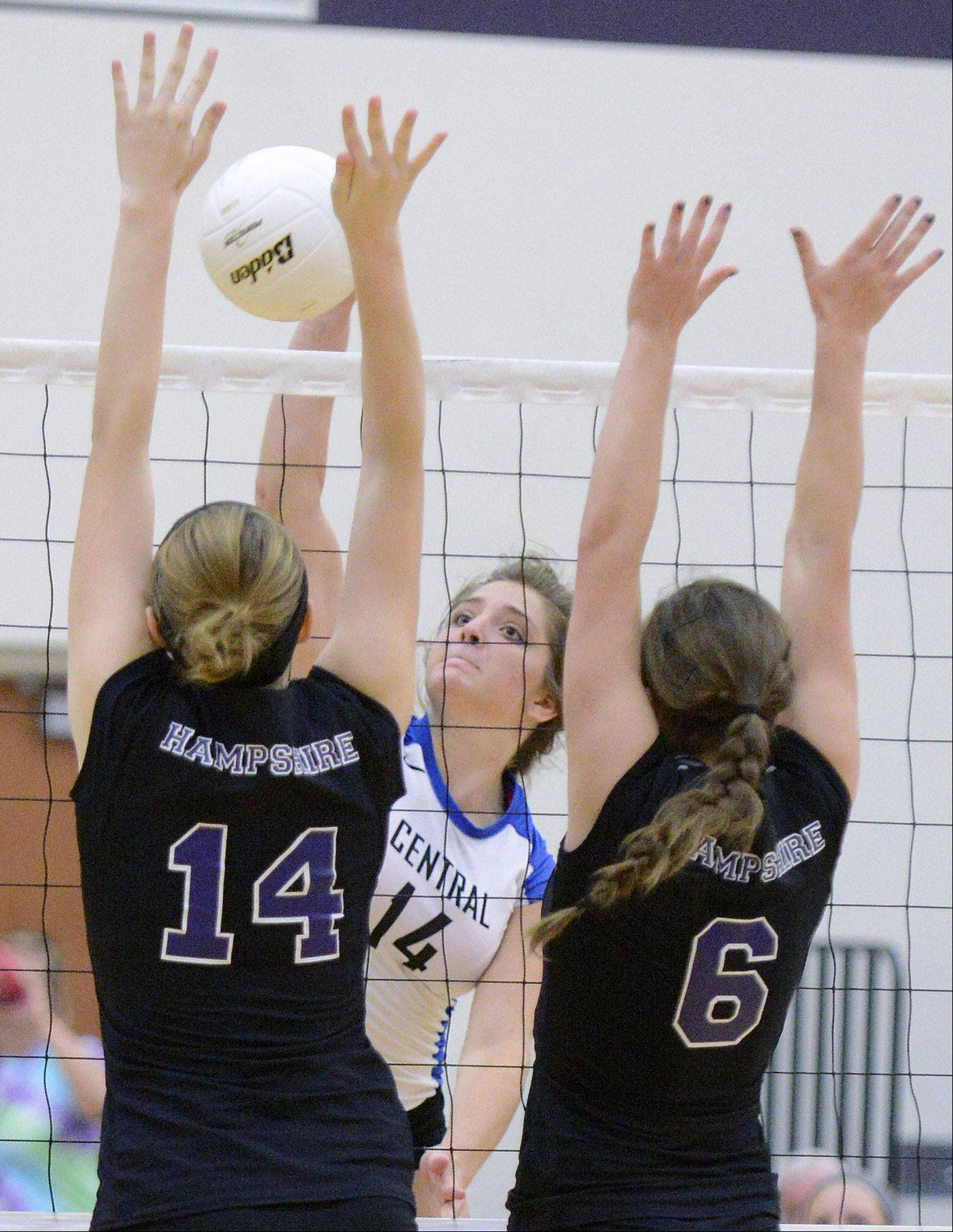 Burlington Central's Lauren Wiltsie spikes over the net toward a block by Hampshire's Sophia Robson, left, and Brittany Laffin in game two on Wednesday, August 28.