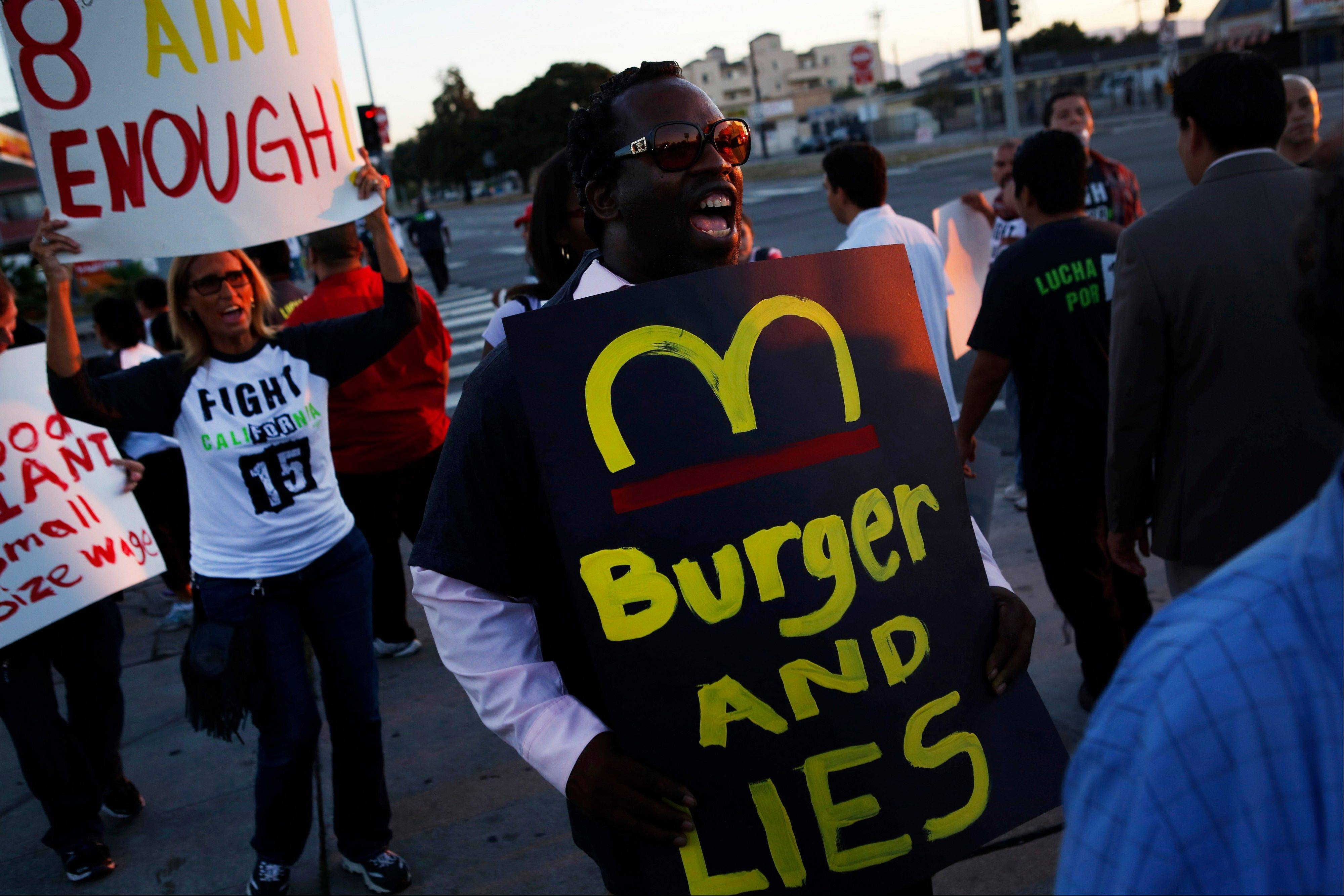 Fast-food workers and supporters protest outside a Burger King in Los Angeles, one of the demonstrations across the country Thursday meant to rachet up pressure on the industry to raise wages.