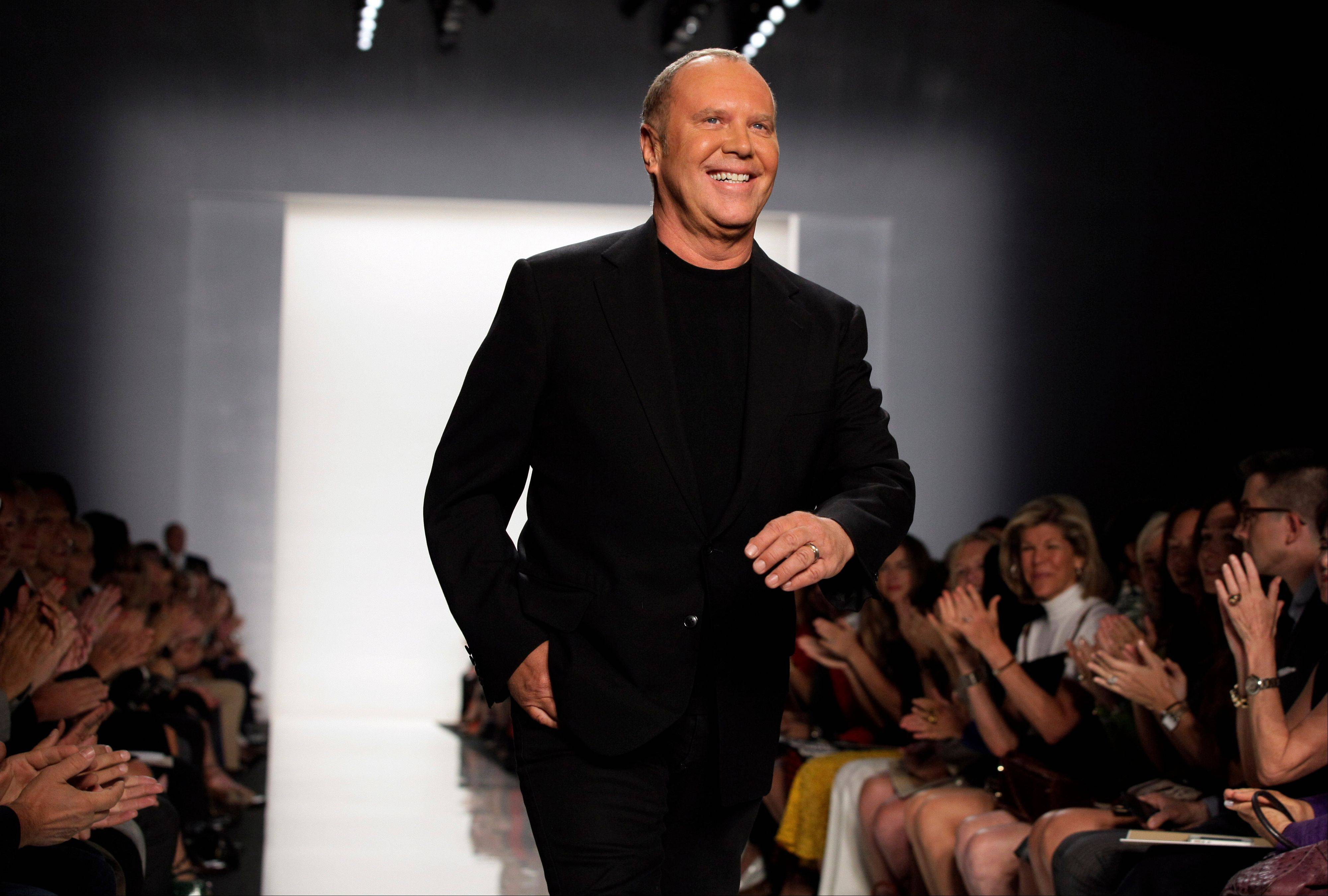 Designer Michael Kors acknowledges applause after his spring 2013 collection was modeled during Fashion Week in New York.