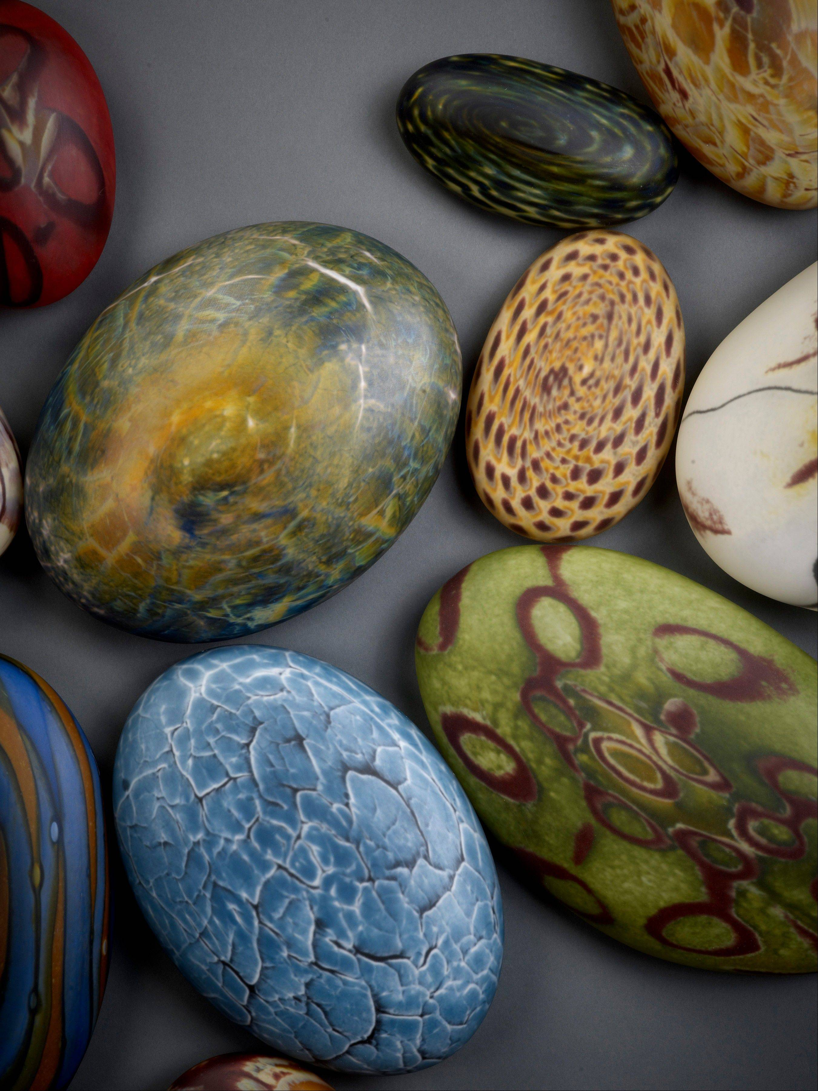 Wet rocks created by Thor and Jennifer Bueno, who form hot glass into shapes evoking water-washed rocks or molecular structures in their studio in Spruce Pine, N.C.