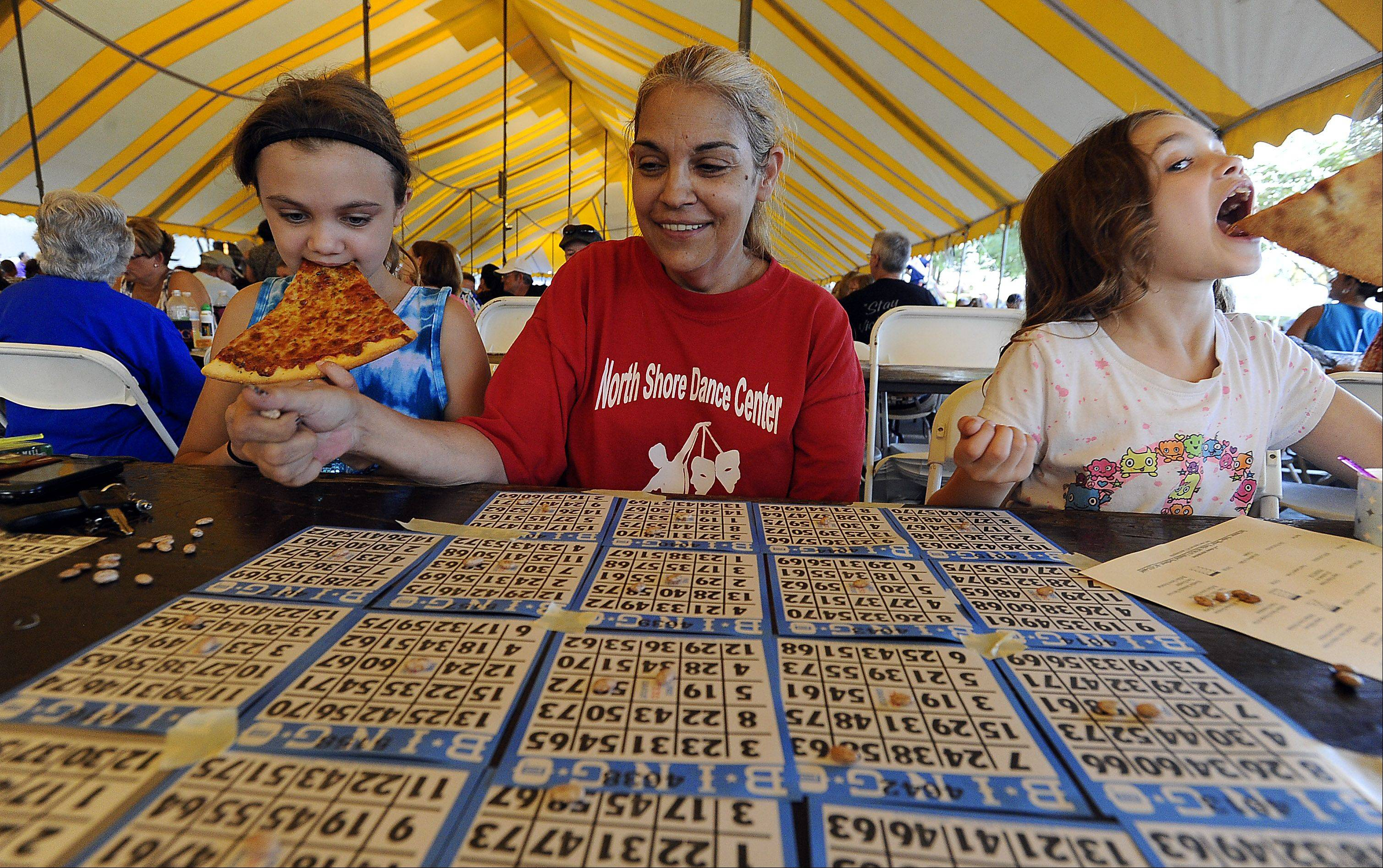 "Bingo and pizza at opening night of Buffalo Grove Days are fun times for Maya Comrov, 10, and her sister Katie, 8, both of Buffalo Grove. Grandmother Patsy Zimmerman of Chicago controls all the beans looking to be the first to scream ""bingo."""