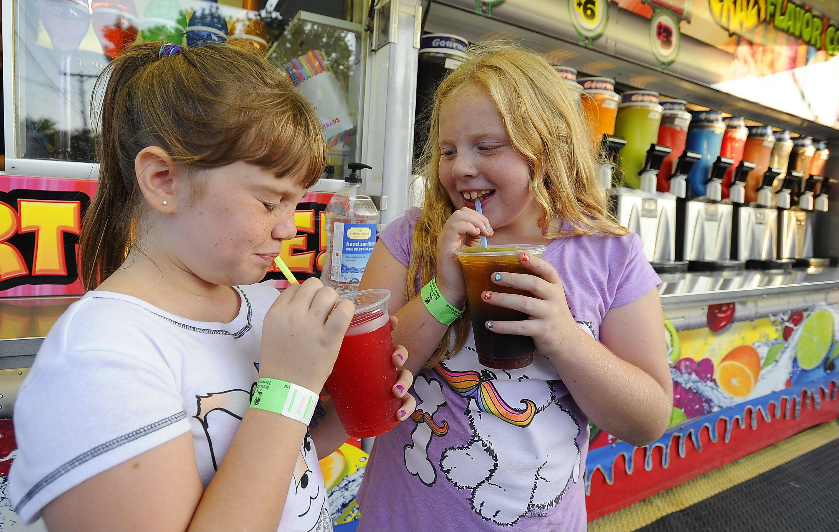 Trying not to get a brain freeze, Maddy Warren, 9, of Lindenhurst and Sabrina Groth, 9, of Buffalo Grove slurp down a slurpee on opening night of Buffalo Grove as summer winds down.