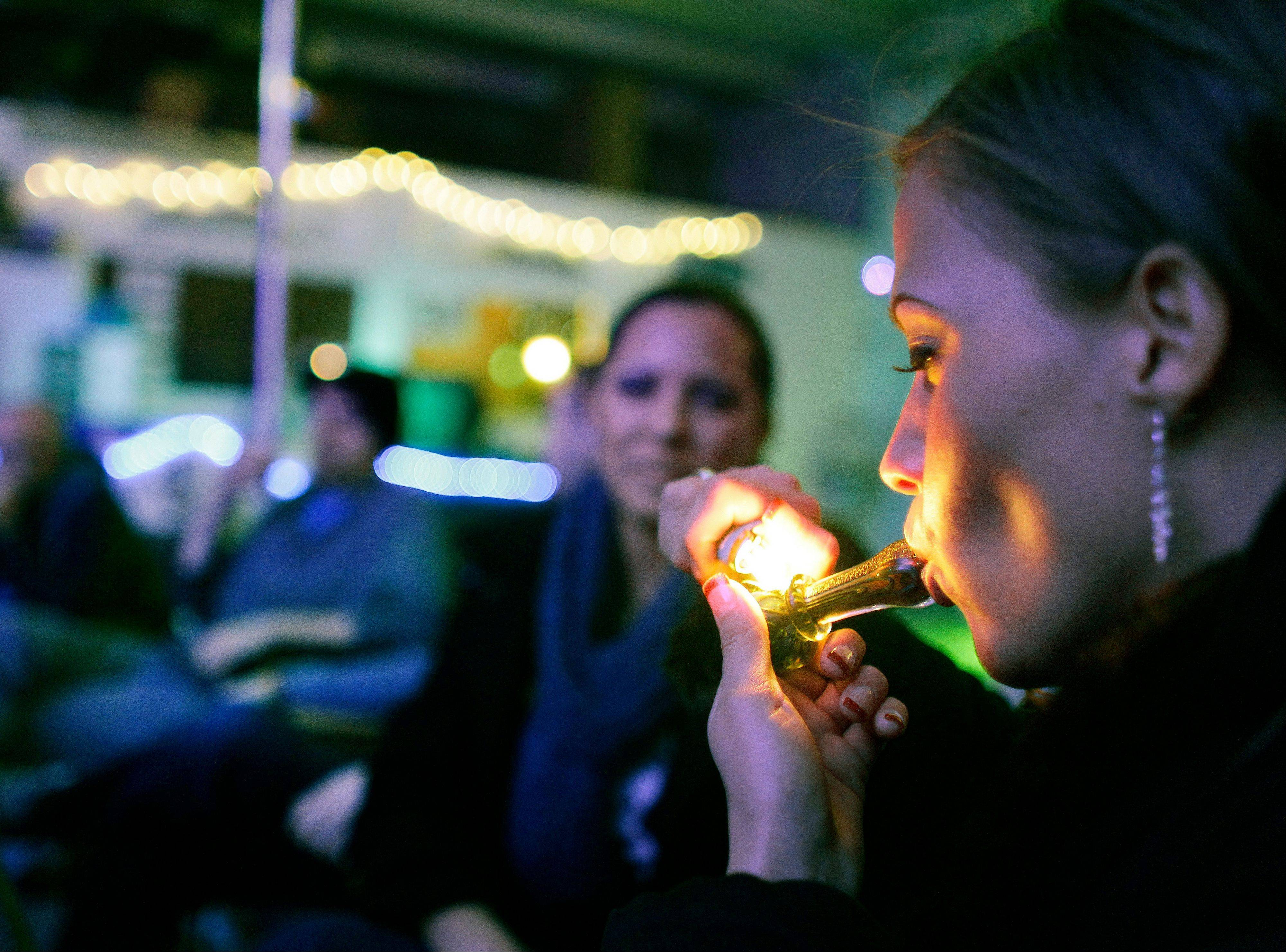 In this in Dec. 31, 2012, file photo, a woman smokes marijuana on the official opening night of Club 64, a marijuana-specific social club, where a New Year's Eve party was held, in Denver.